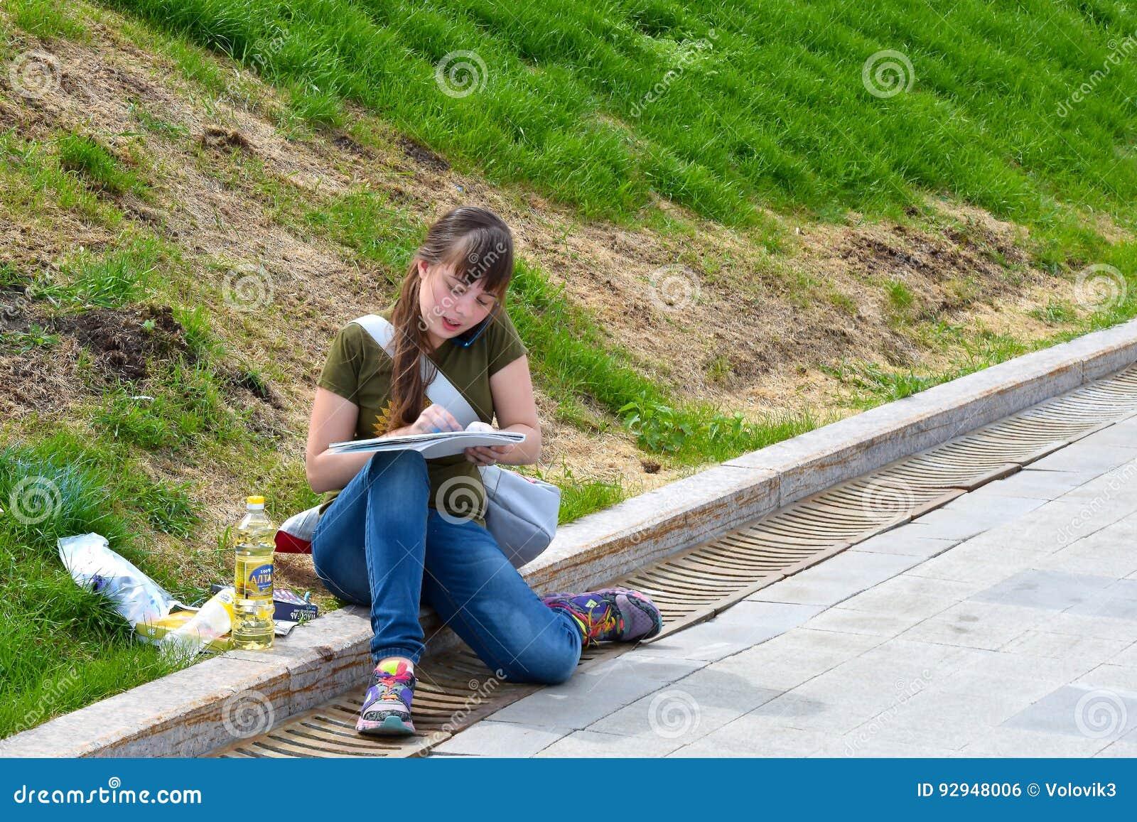 Den unga konstnären arbetar på universitetinvallningen av floden