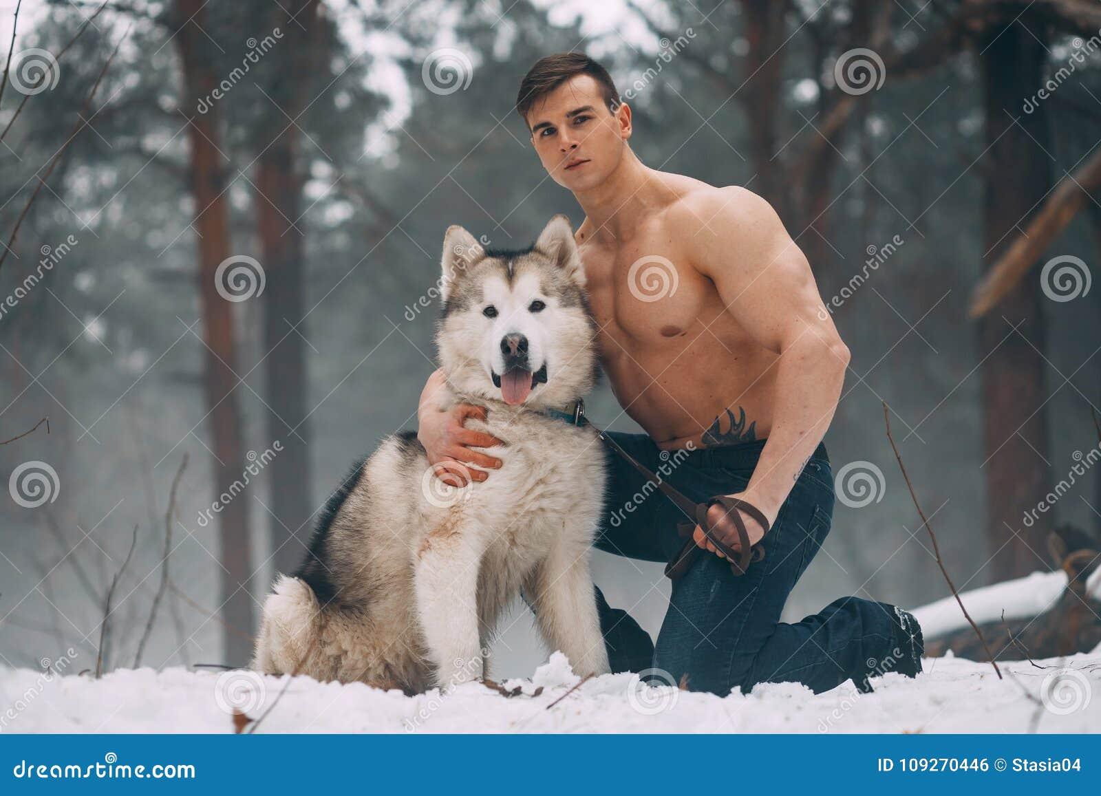 Den unga kroppsbyggaren med den kala torson omfamnar hunden som malamuten på går i vinterskog