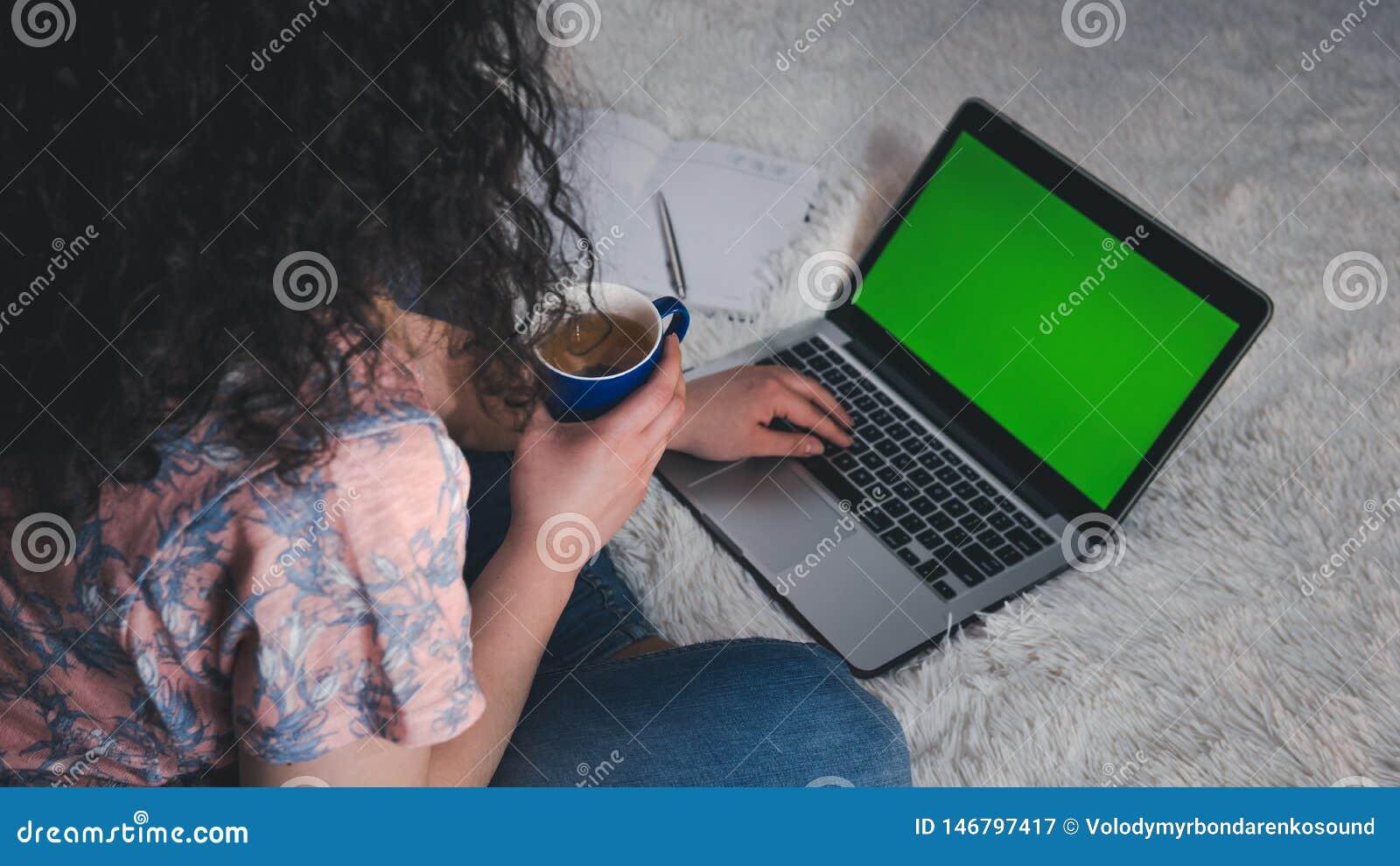 Den unga kvinnan anv?nder en b?rbar dator hemma B?rbara datorn med den gr?na sk?rmen