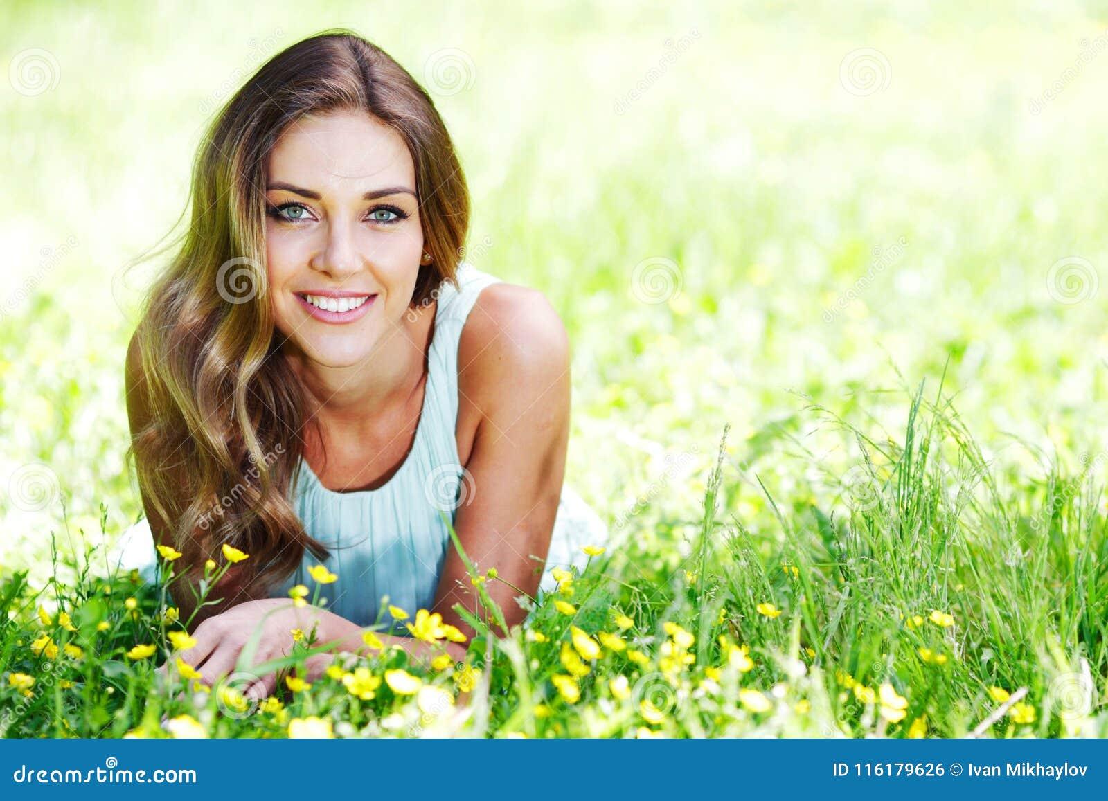 Den unga kvinnan i blått klär att ligga på gräs