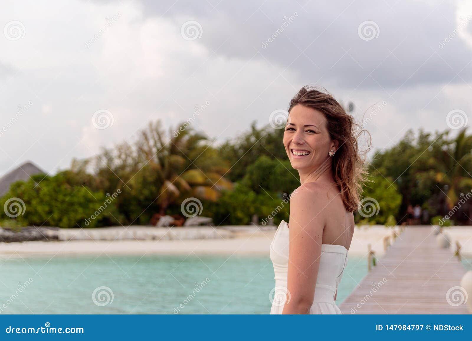 Den unga kvinnan i br?llopsresa kopplar av p? en pir som ser solnedg?ngen