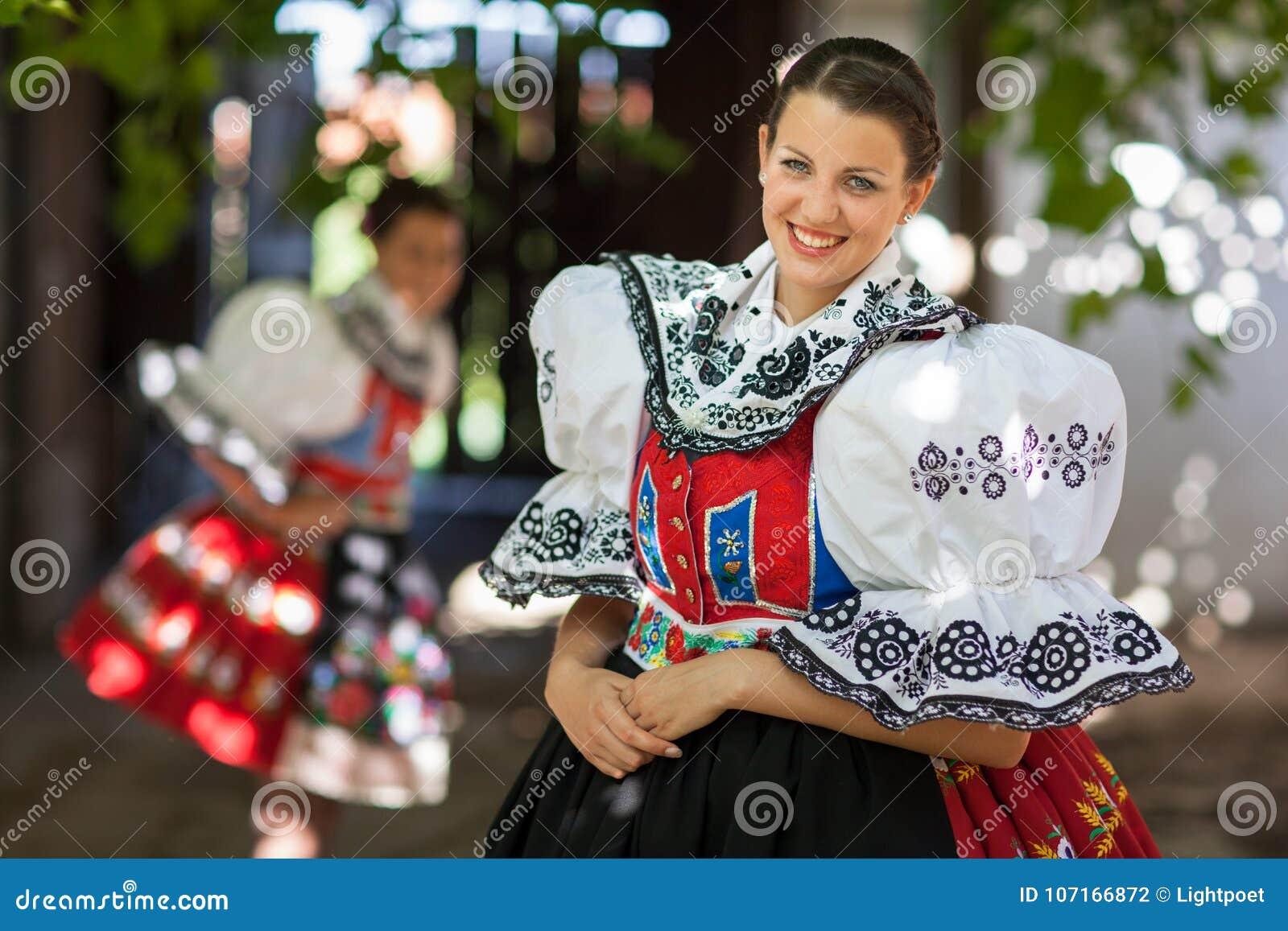 Den unga kvinnan i en rikt dekorerad ceremoniell folk klär