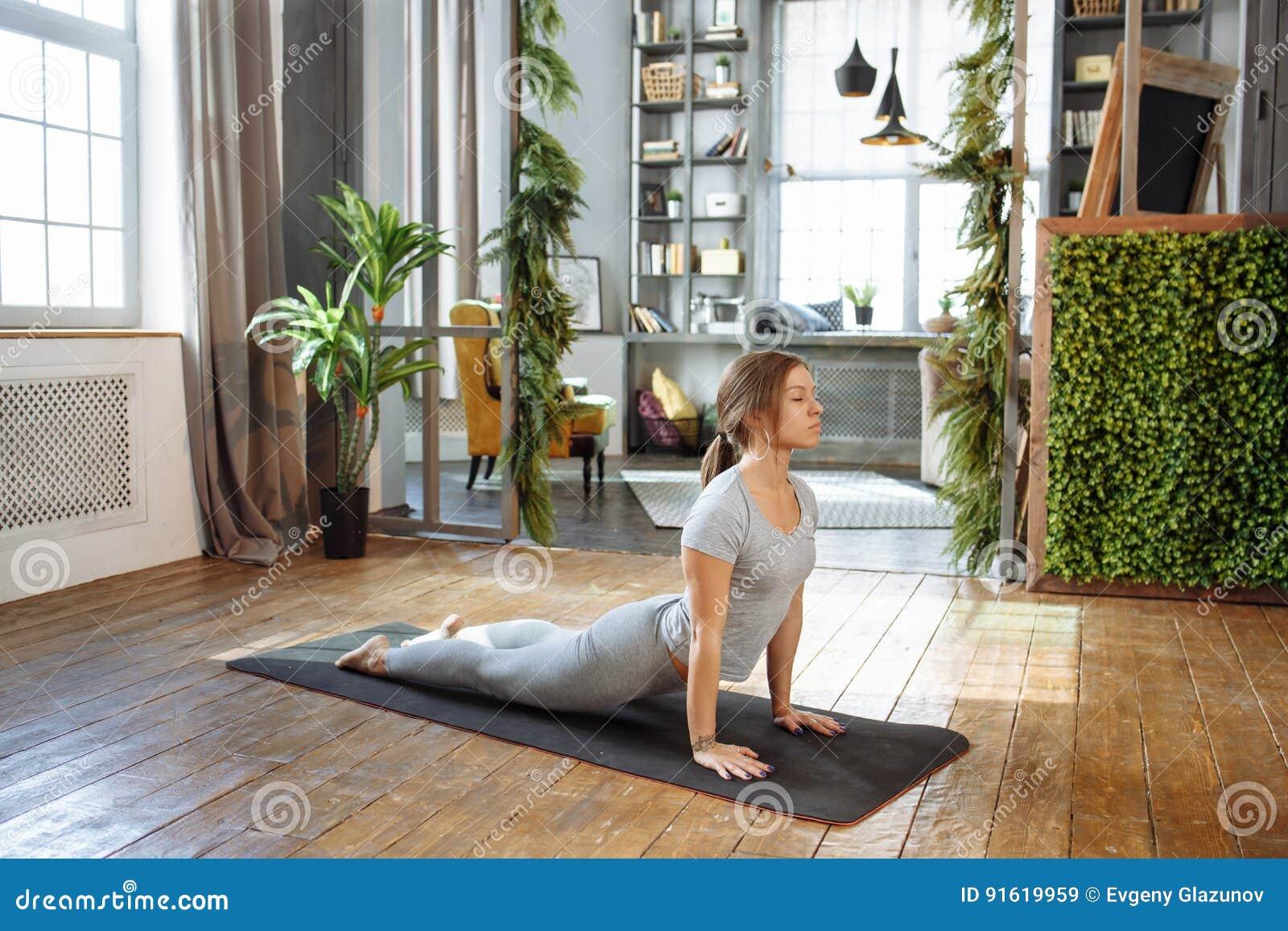Den unga kvinnan i praktiserande jämviktsyoga för homeware poserar på matta i hennes väl till mods sovrum