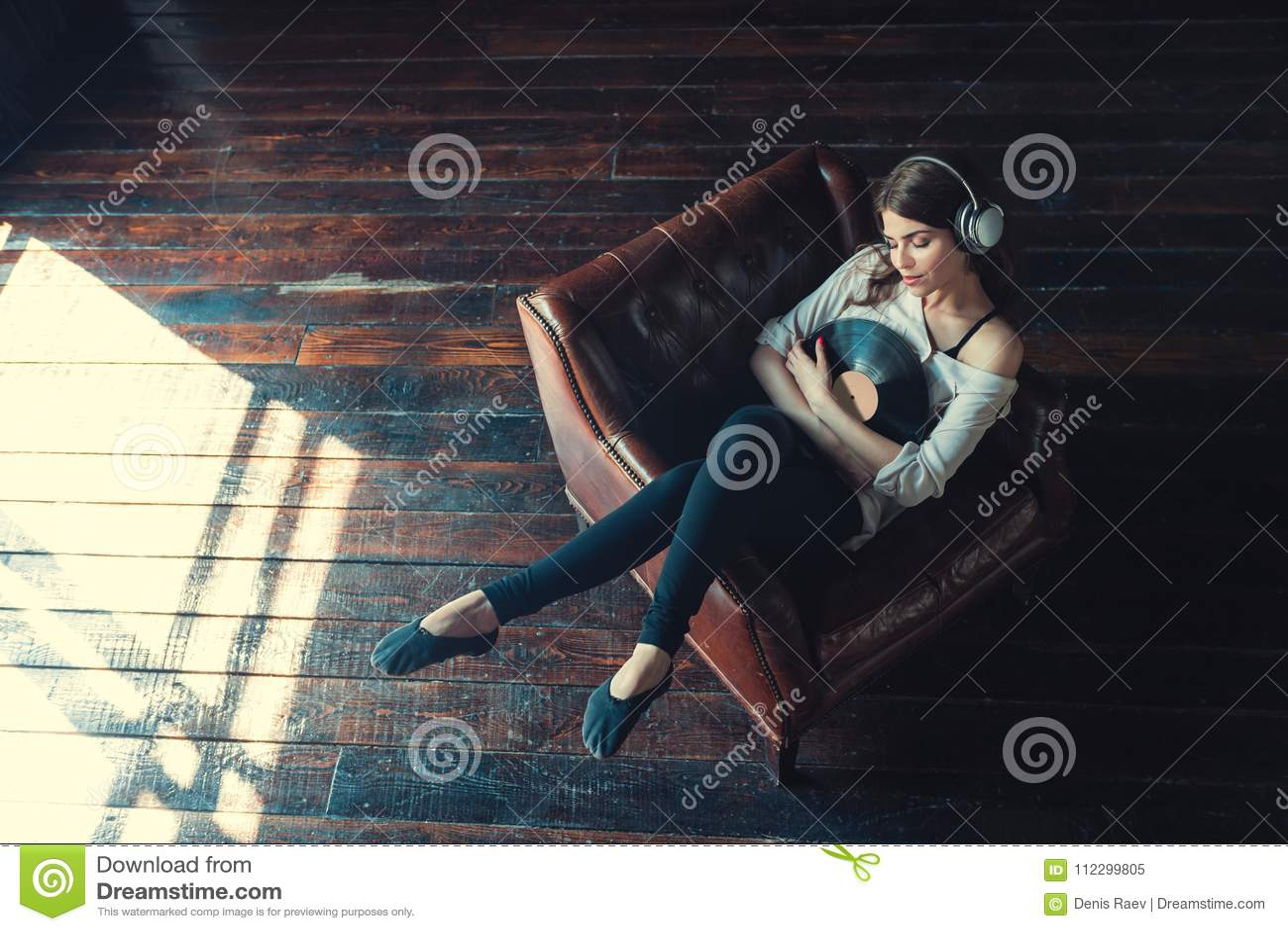 Den unga kvinnan lyssnar till musik inomhus