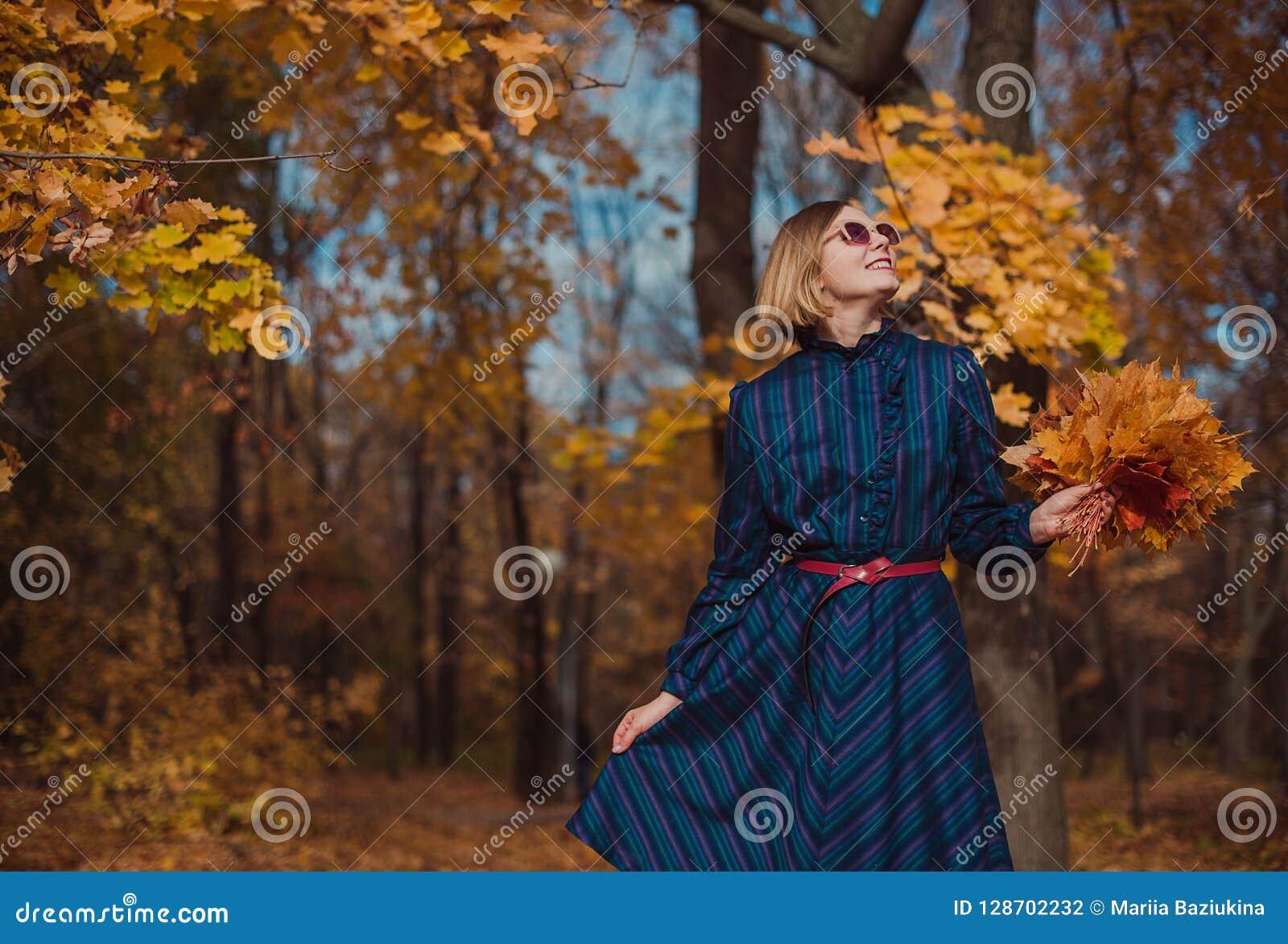 Den unga kvinnan med den bärande blåttklänningen för blont hår som går i höst, parkerar