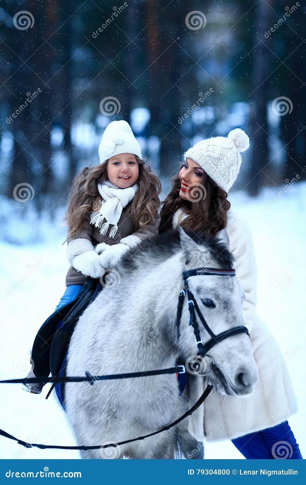 Den unga kvinnan och flickan går med miniatyrhästen i vinter parkerar