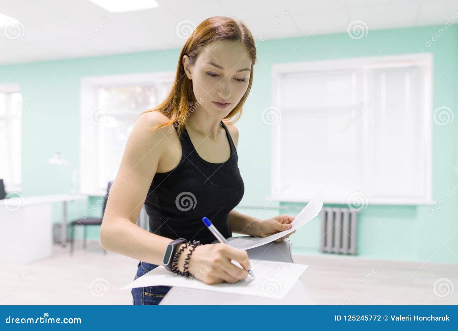 Den unga kvinnan rymmer en salong för omsorgen av händer och spikar teckenlegitimationshandlingar, sätter ett häfte