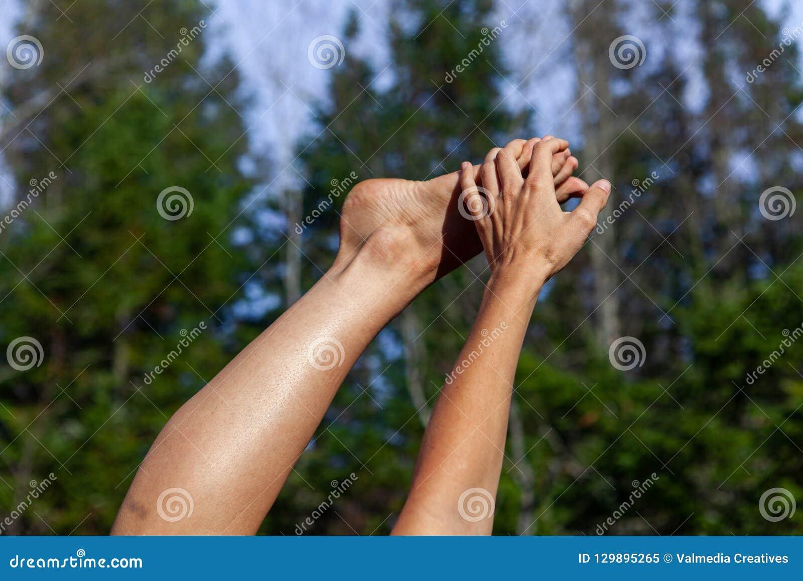 Den unga kvinnan rymmer hennes fot upp i luften, medan tycka om solen