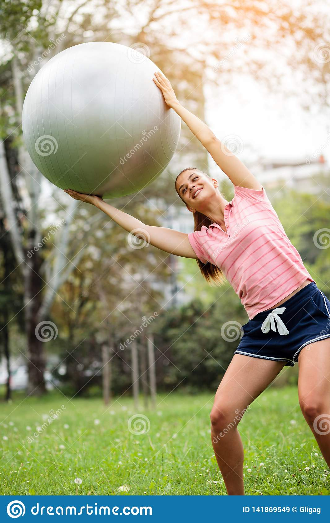 Den unga kvinnan som övar med pilatesbollen i, parkerar Yogainstruktör som rymmer konditionbollen över hennes huvud och utbildnin