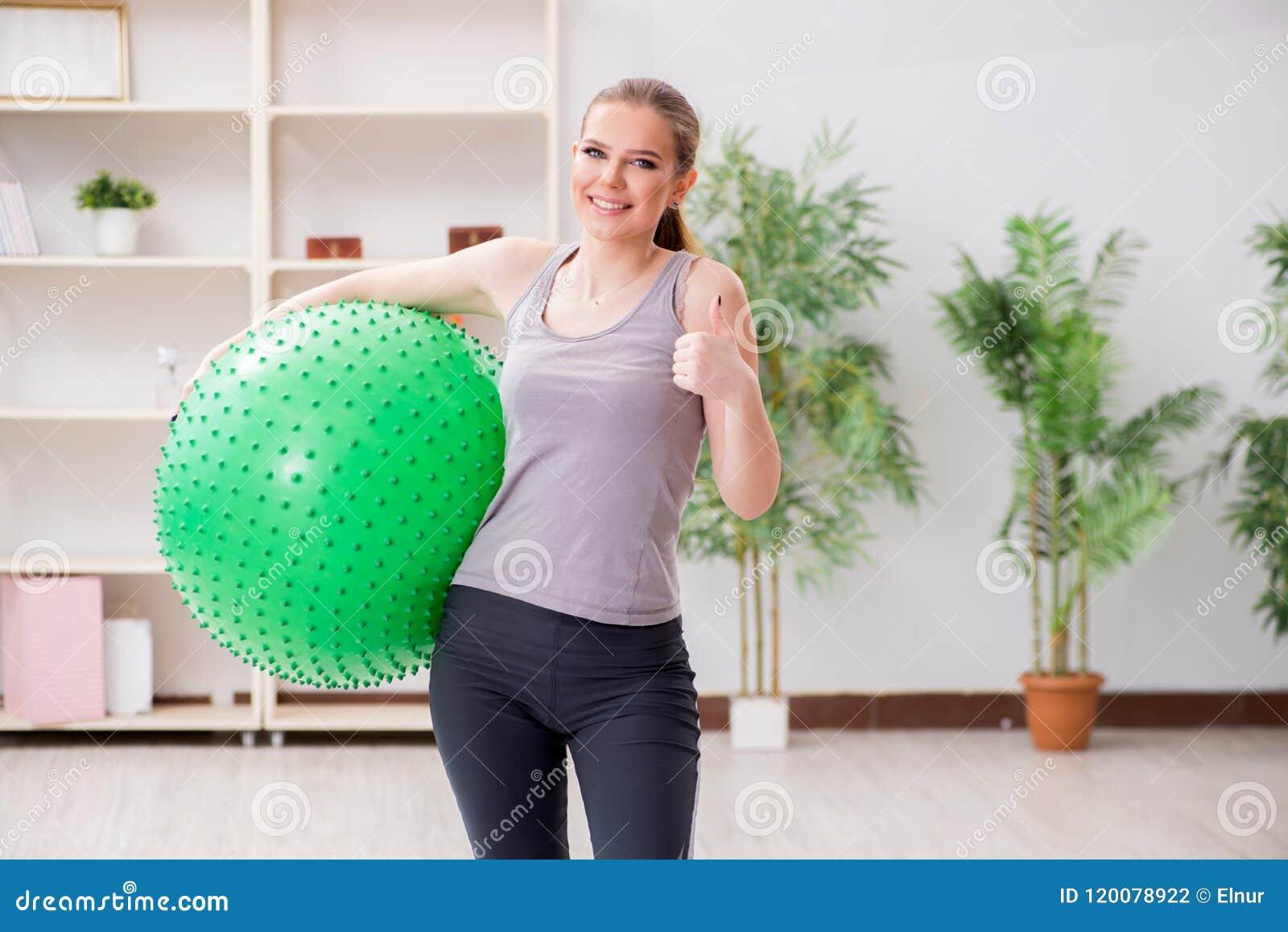 Den unga kvinnan som övar med stabilitetsbollen i idrottshall