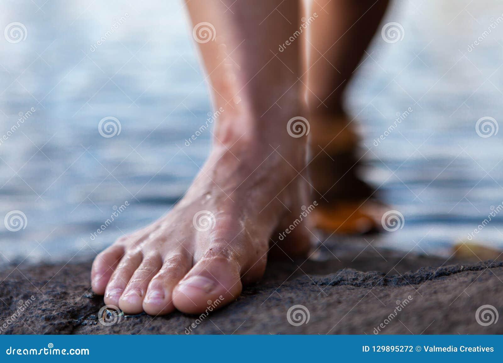 Den unga kvinnan som går ut ur den kala foten för vatten på, vaggar