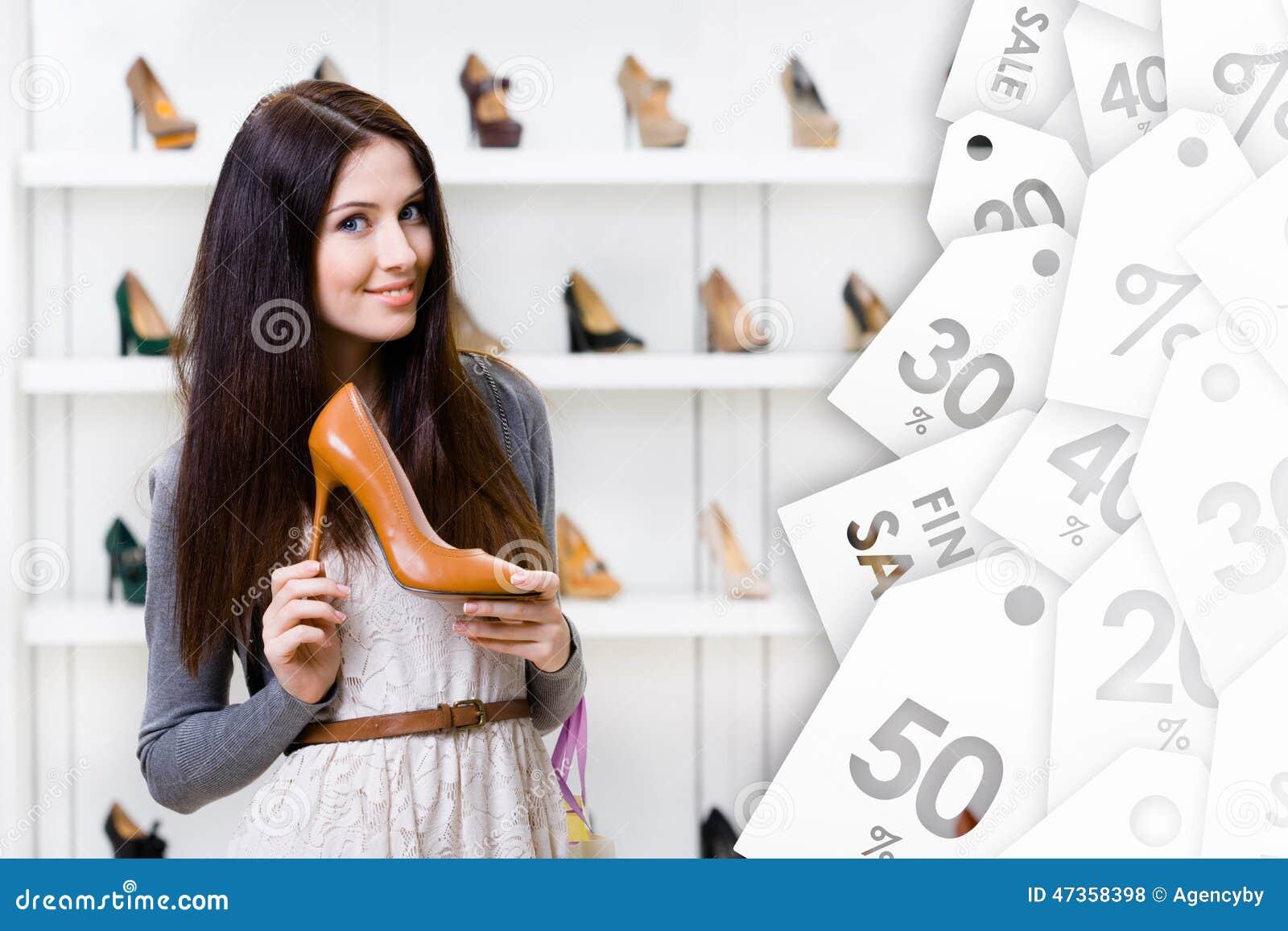 Den unga kvinnan som håller höjdpunkt, heeled skon på försäljning