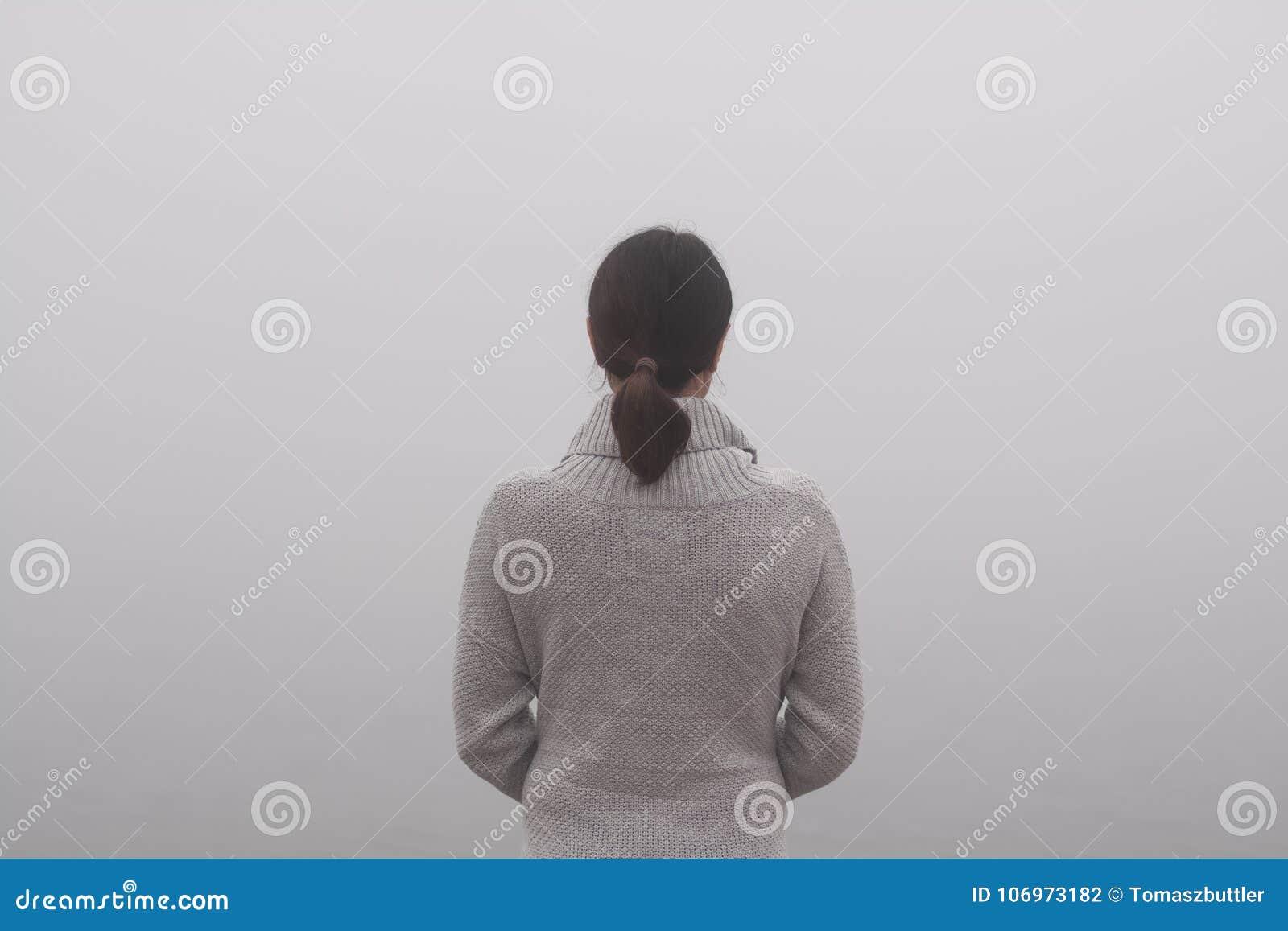 Den unga kvinnan står vid vattnet på en dimmig dag