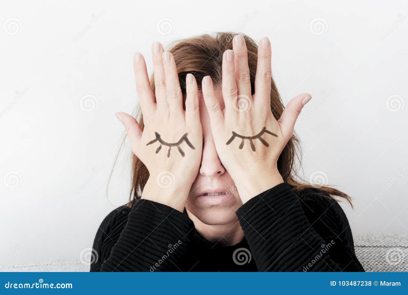 Den unga kvinnan täcker som henne, gömma i handflatan ögon med henne Ögon som målas på hennes hand