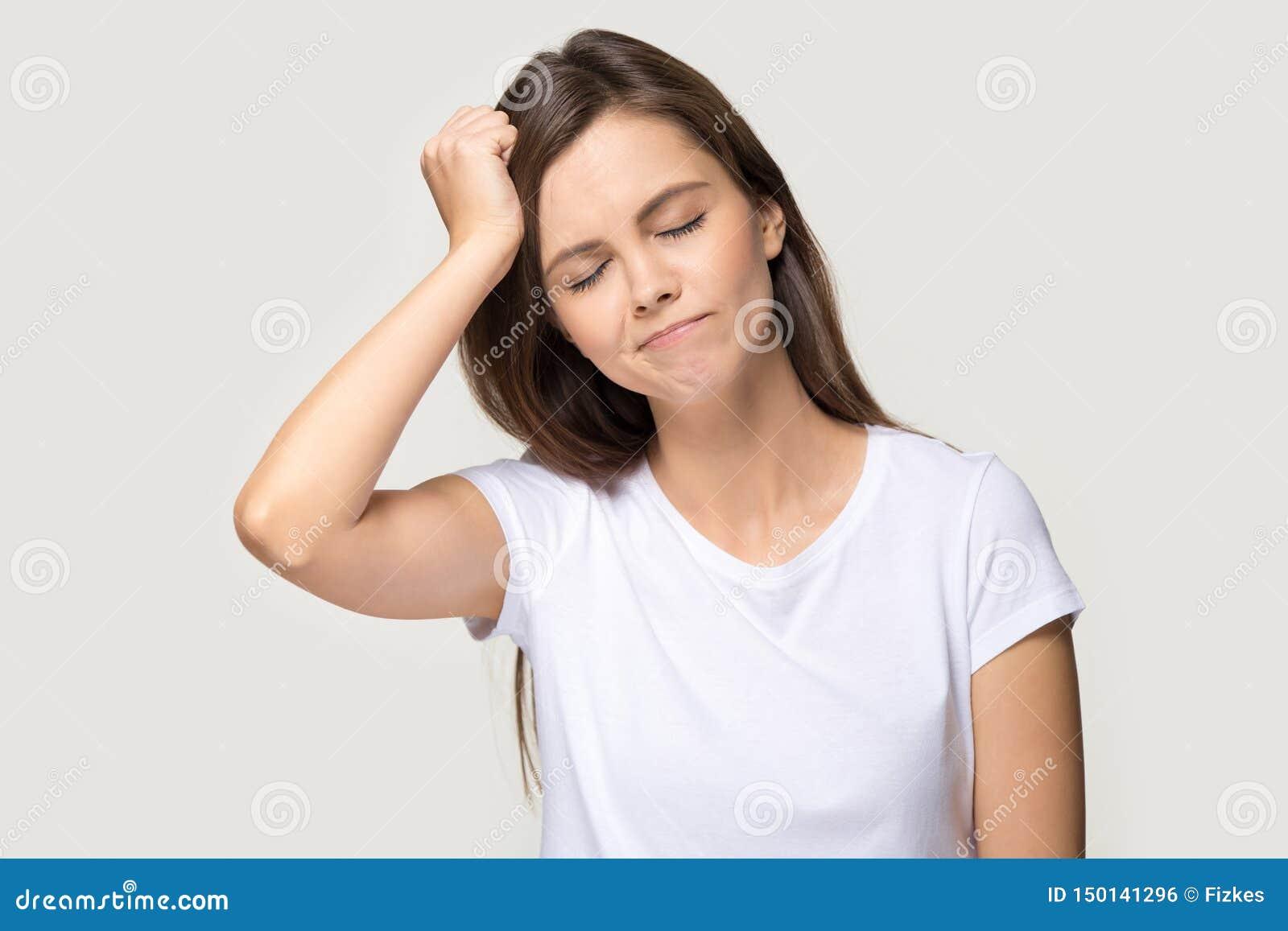 Den unga kvinnan trycker på huvudet med handen glömde något studioskottet