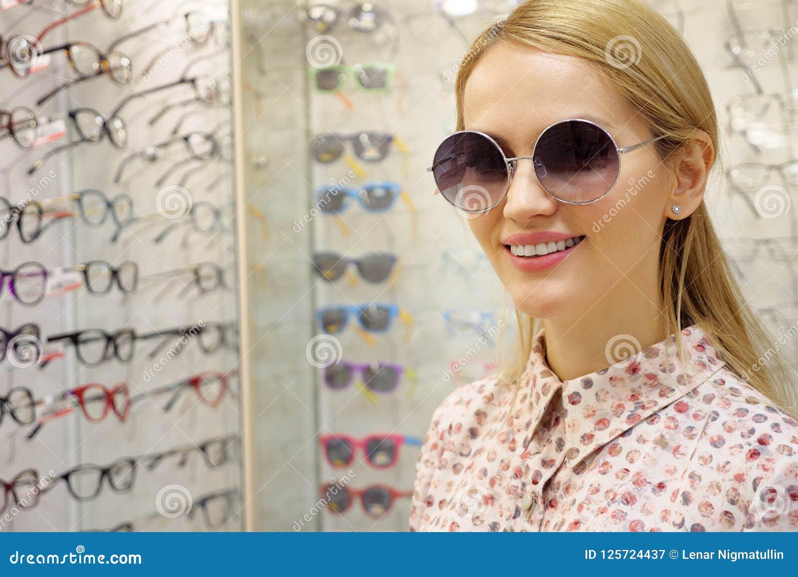 Den unga kvinnan väljer sol- exponeringsglas i optikerlager