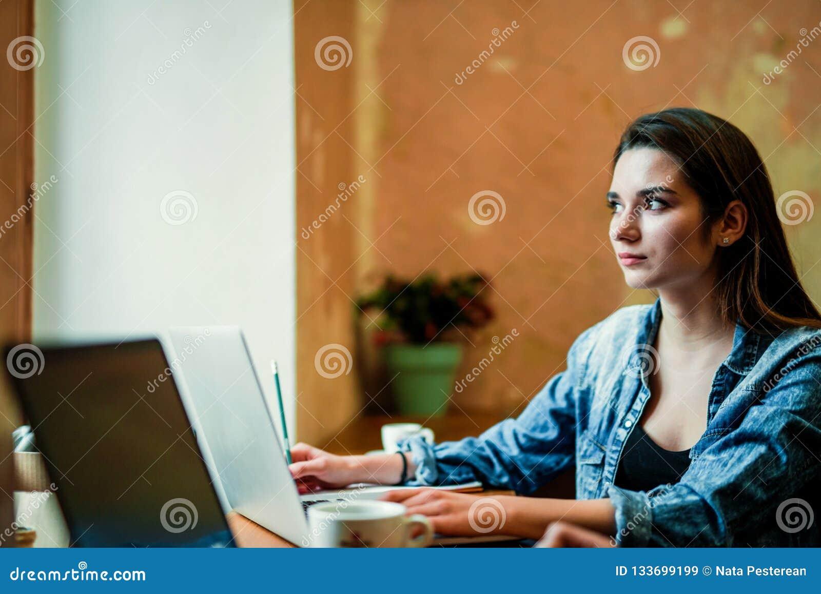 Den unga kvinnliga studenten sitter nära fönstret med bärbara datorn och blick till och med fönstret