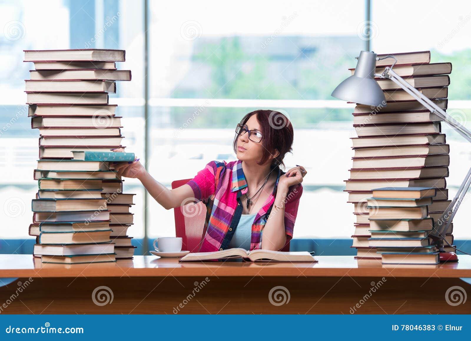 Den unga kvinnliga studenten som förbereder sig för examina