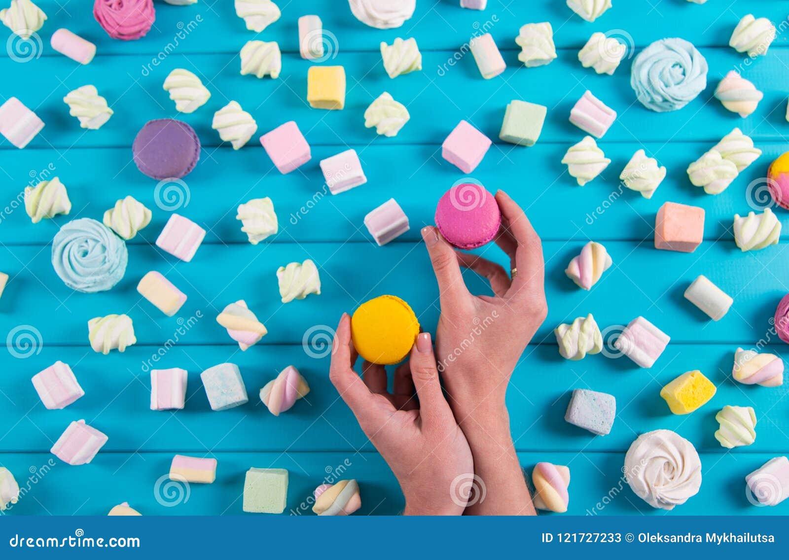 Den unga kvinnlign räcker att rymma två vibrerande makron med mycket fyrkantig färgrik marshmallow på blå bakgrund