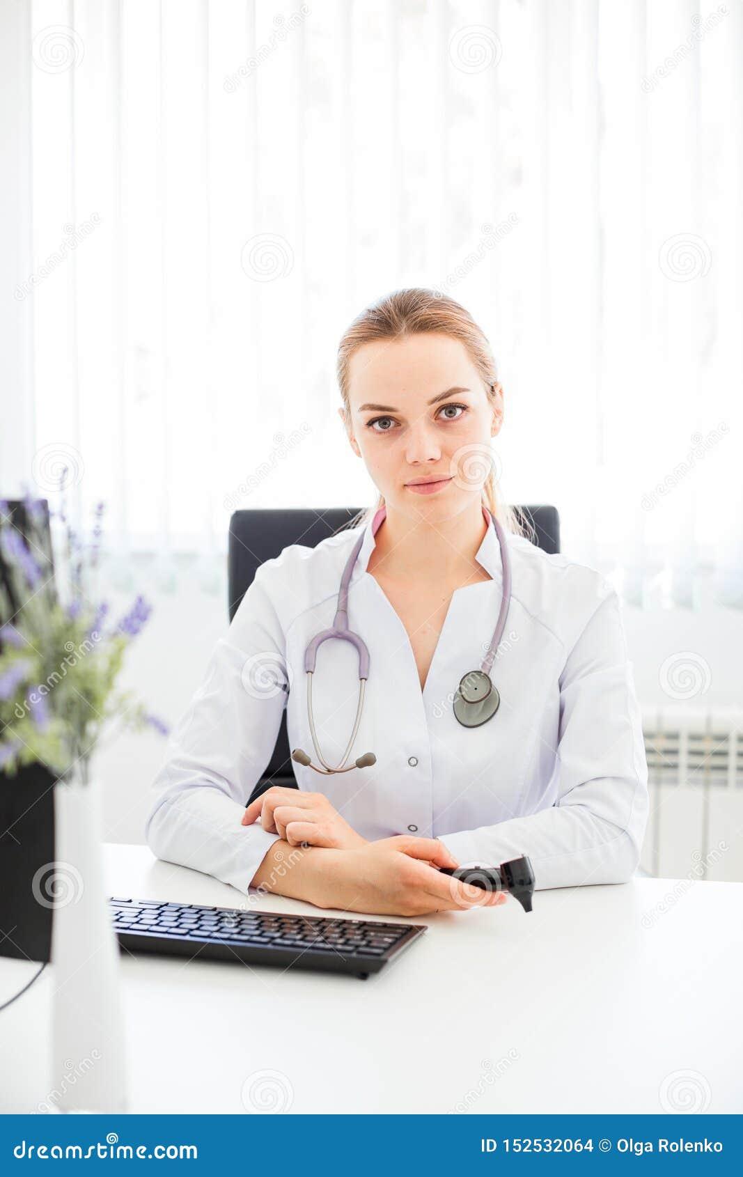 Den unga le doktorn som sitter på skrivbordet på en svart stol med hennes armar, korsade