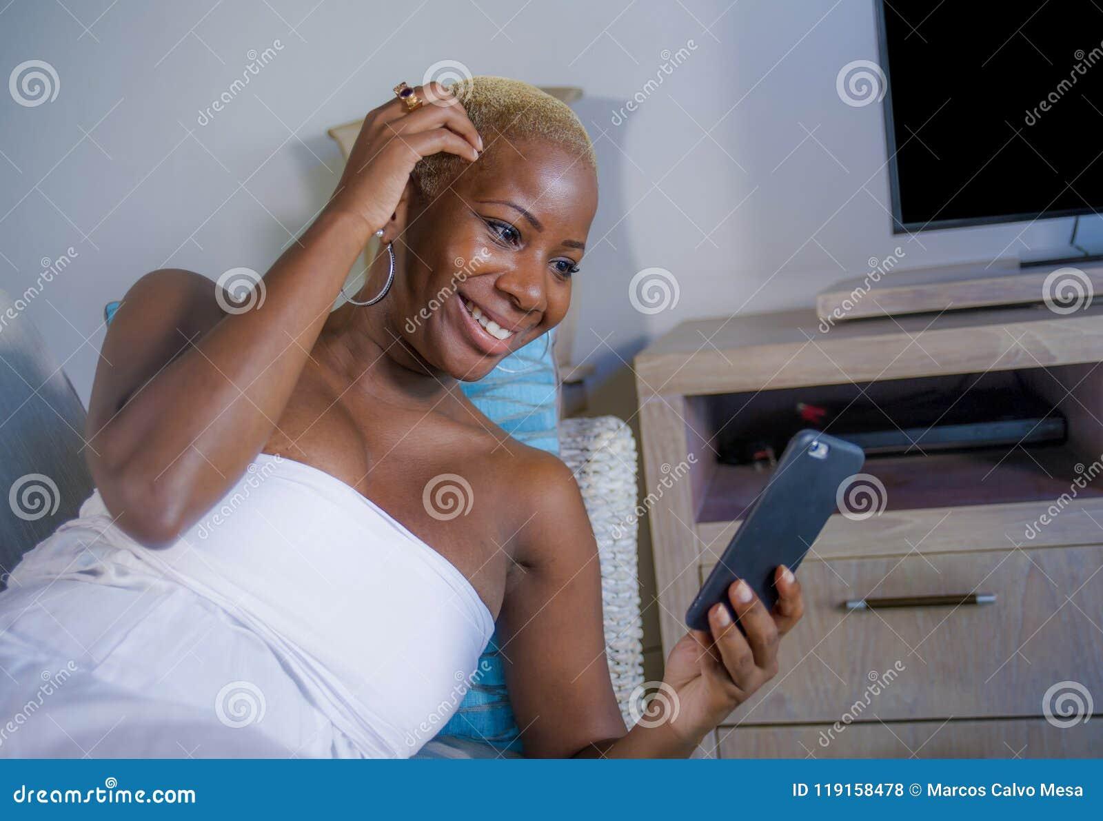Den unga liggande hemmastadda soffan för den härliga och lyckliga svarta afro amerikanska kvinnan kopplade av att le gladlynt anv