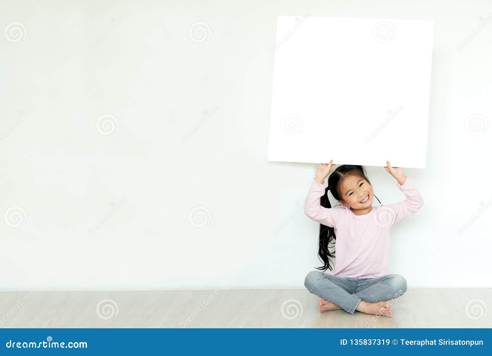 Den unga lilla asiatiska flickan eller ungen tycker om att rymma upp det tomma vita plakatbrädet för massmediabaner, affärsinnehå