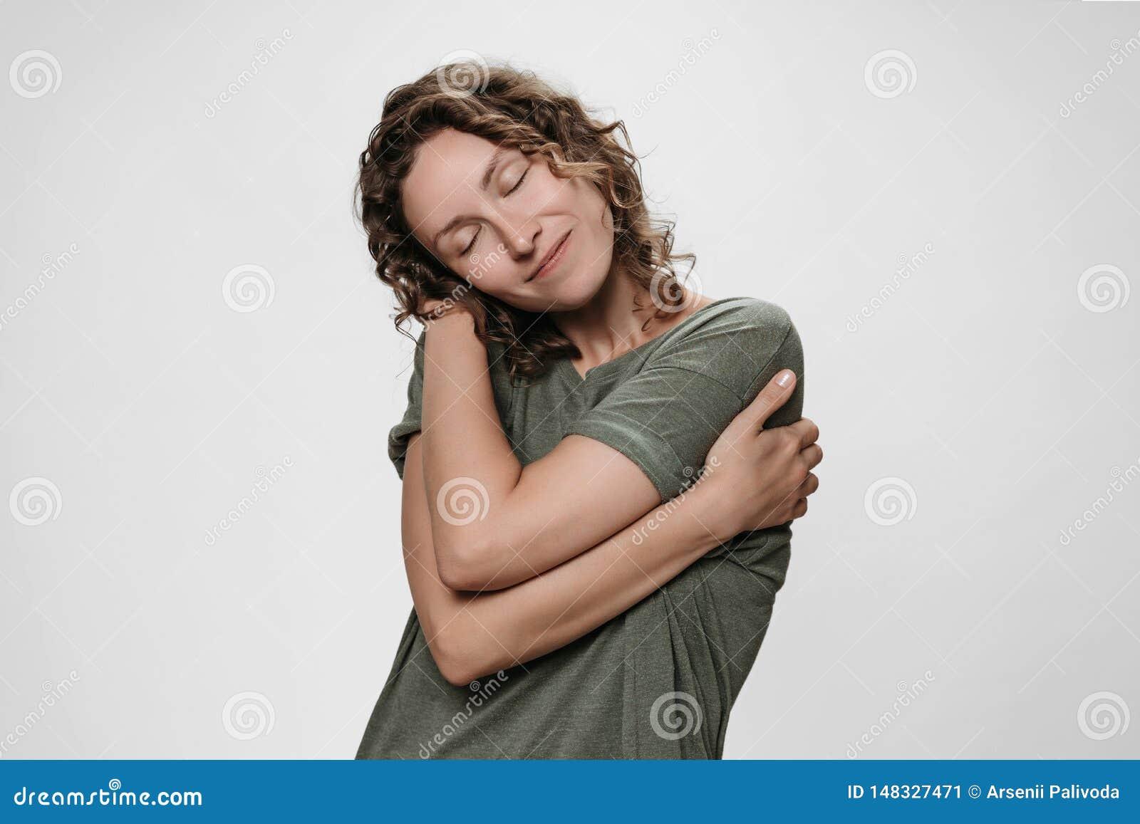 Den unga lockiga kvinnan som kramar sig, ser lycklig, älskar sig, har hög självaktning