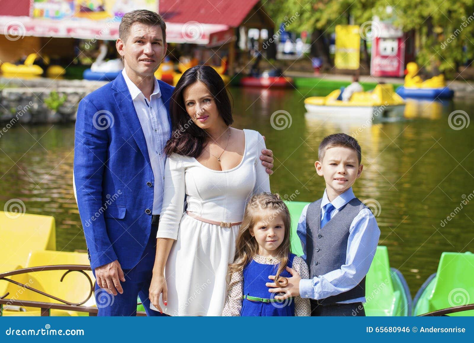 Den unga lyckliga familjståenden på bakgrund av hösten parkerar