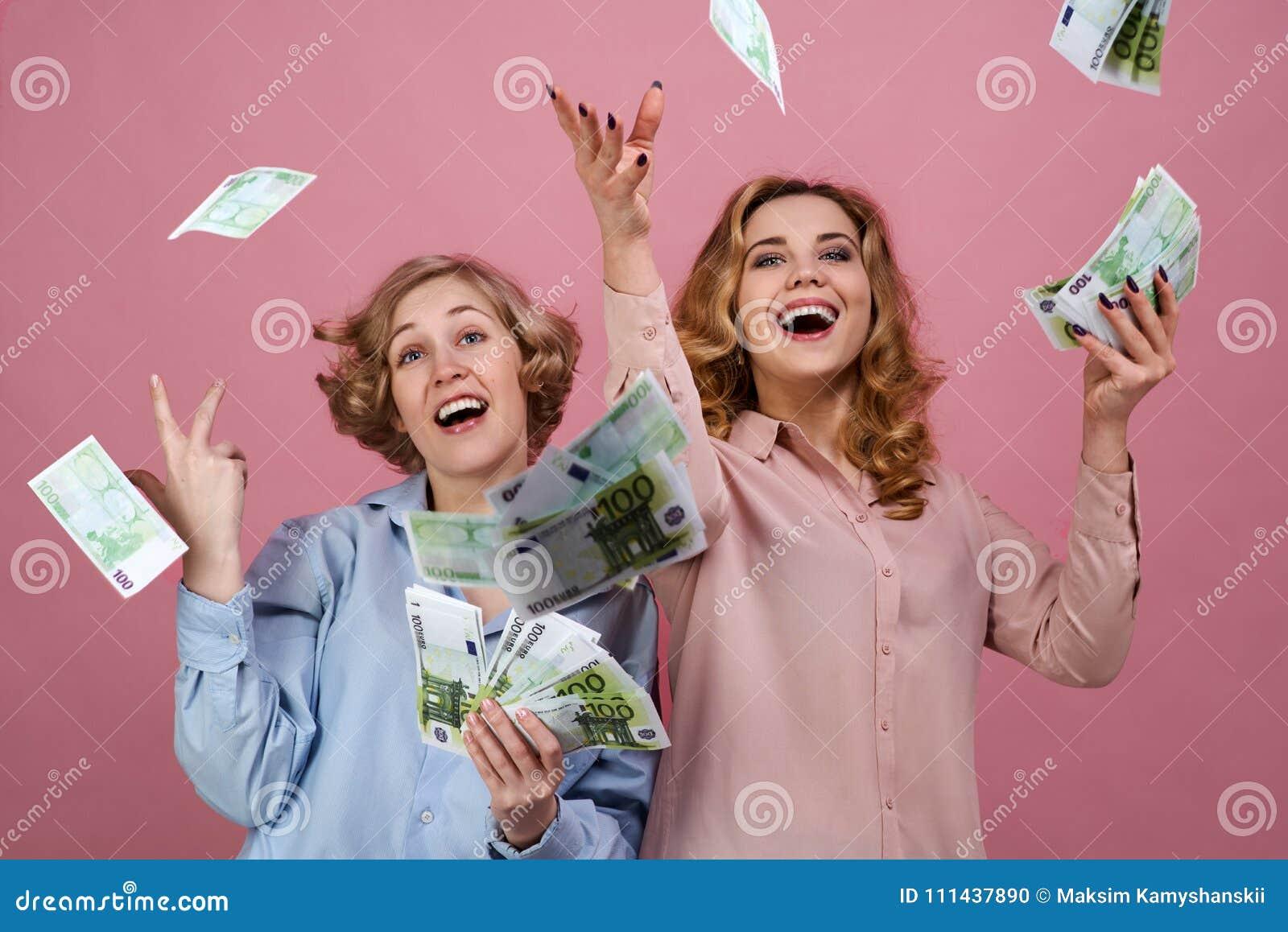 Den unga lyckliga flickan med fröjd kastar upp kassan De tycker om framgång och välstånd, finansmarknader och den vinnande lotter
