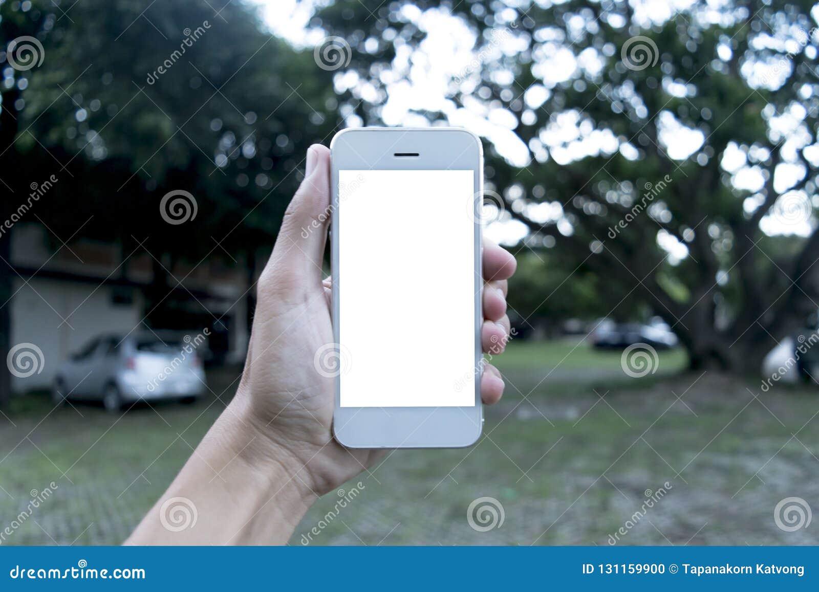 Den unga mannen använder hans mobiltelefon för att ta bilder av hans minnen och för att se dem i framtiden