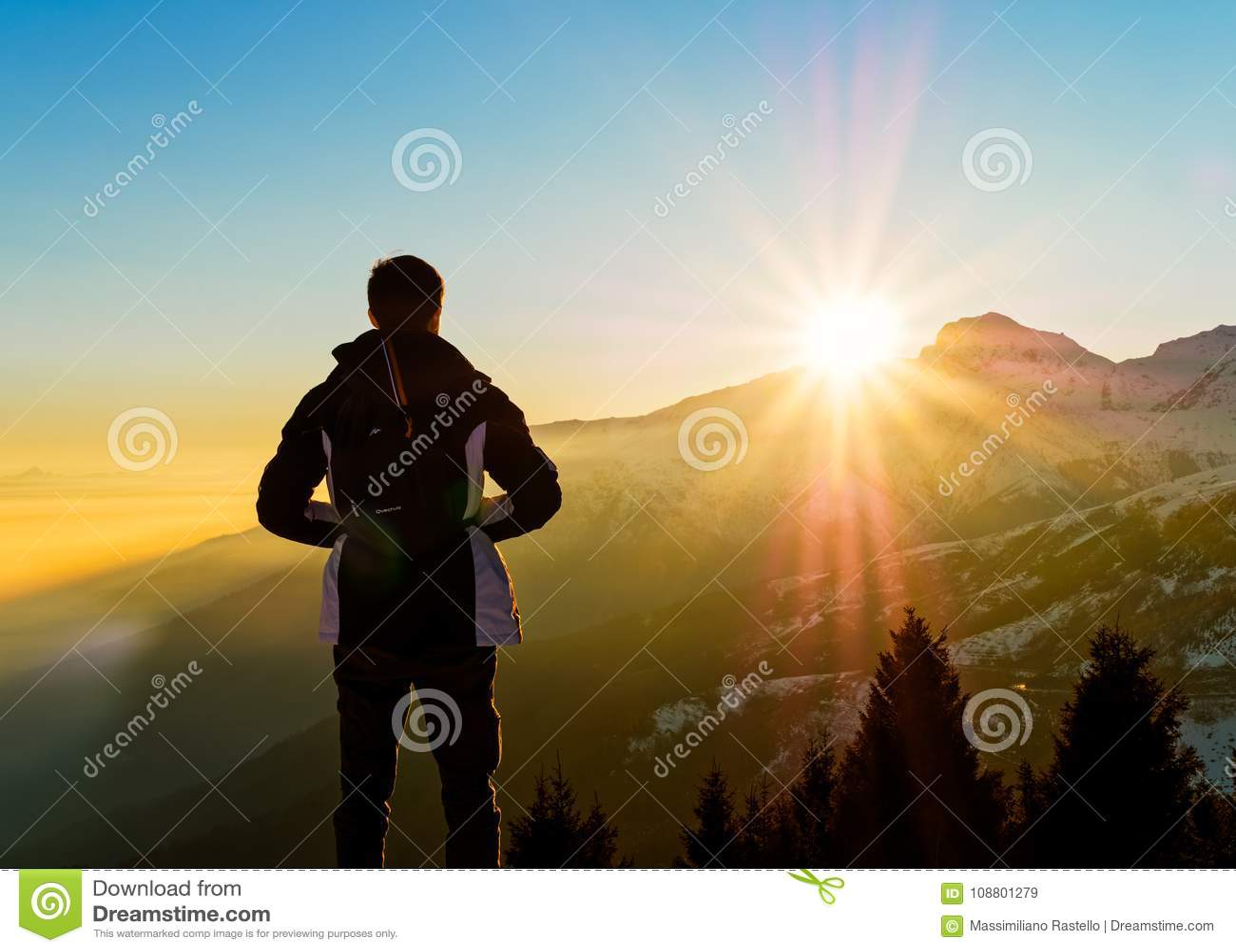 Den unga mannen beskådar solnedgång på fjällängarna