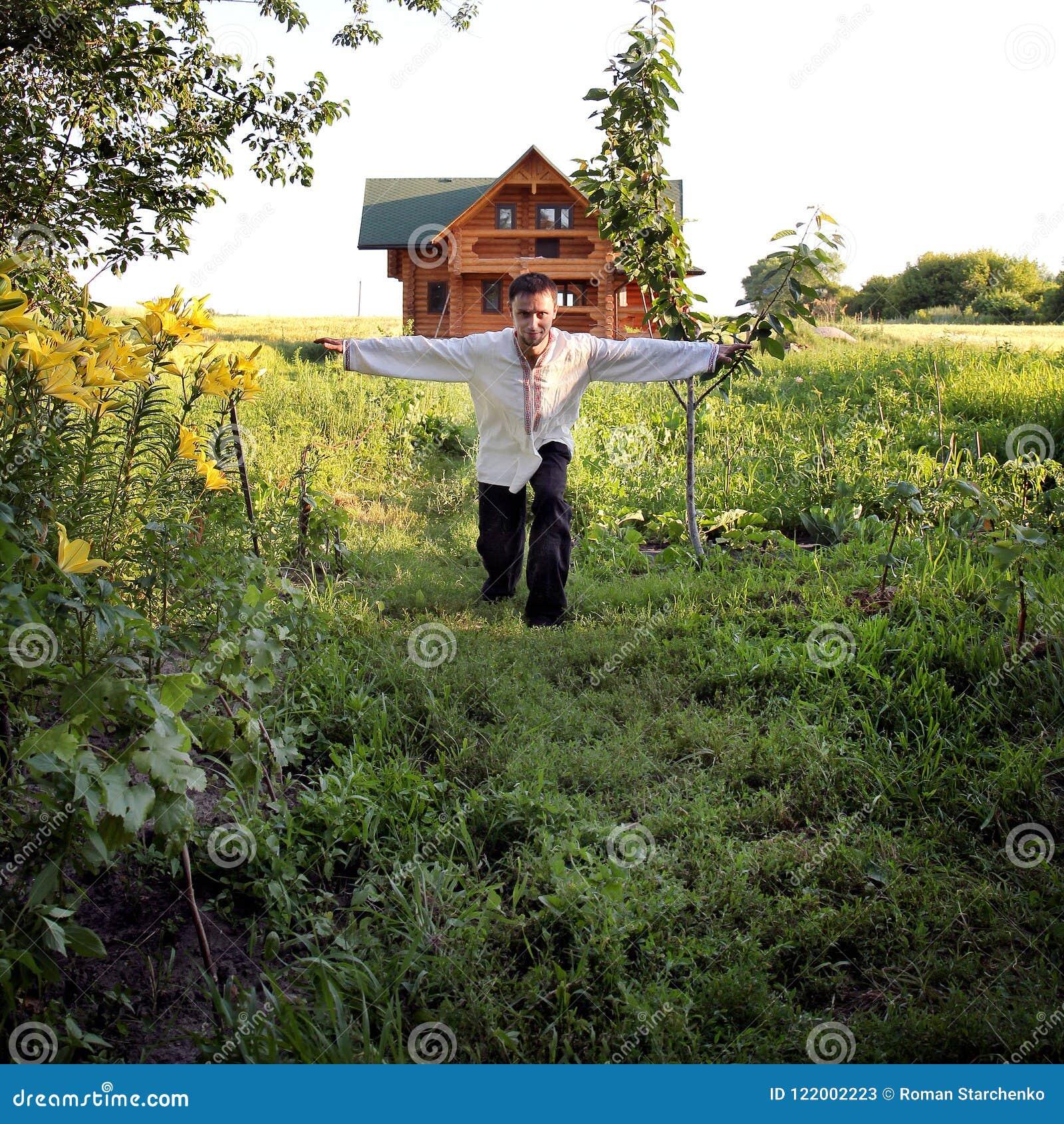 Den unga mannen i broderad skjorta poserar på kamera bland gröna växter