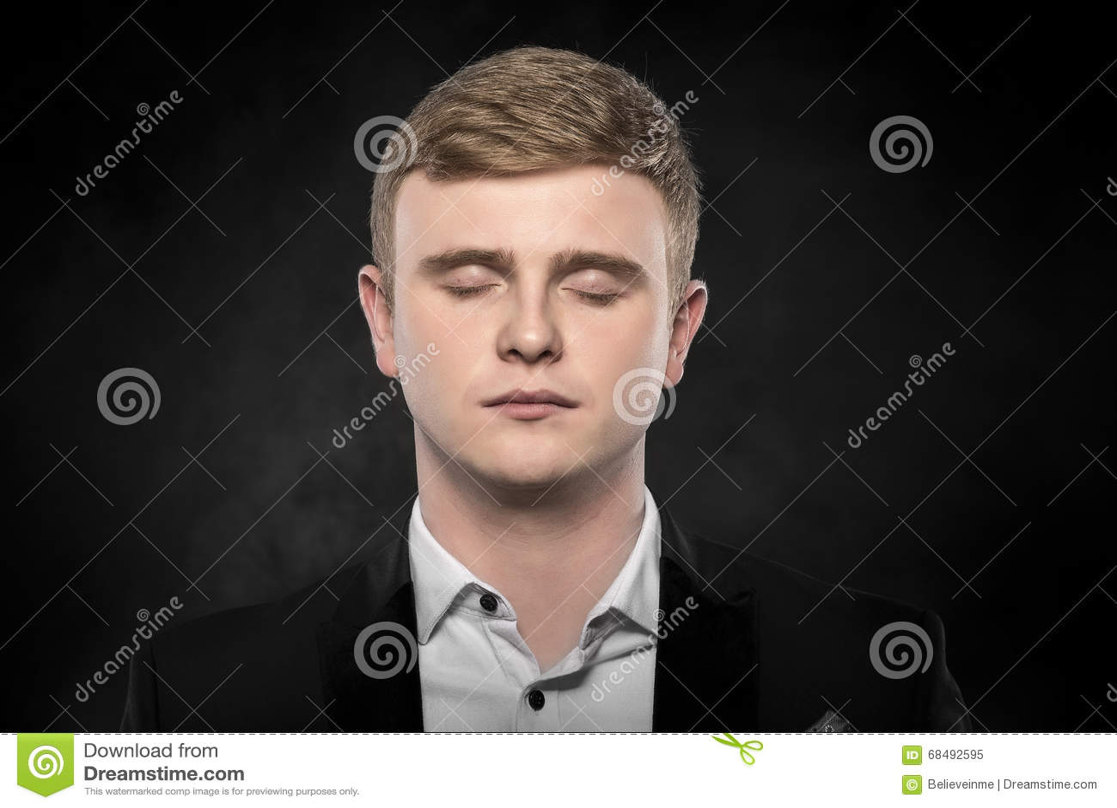 Den unga mannen i en dräkt sover