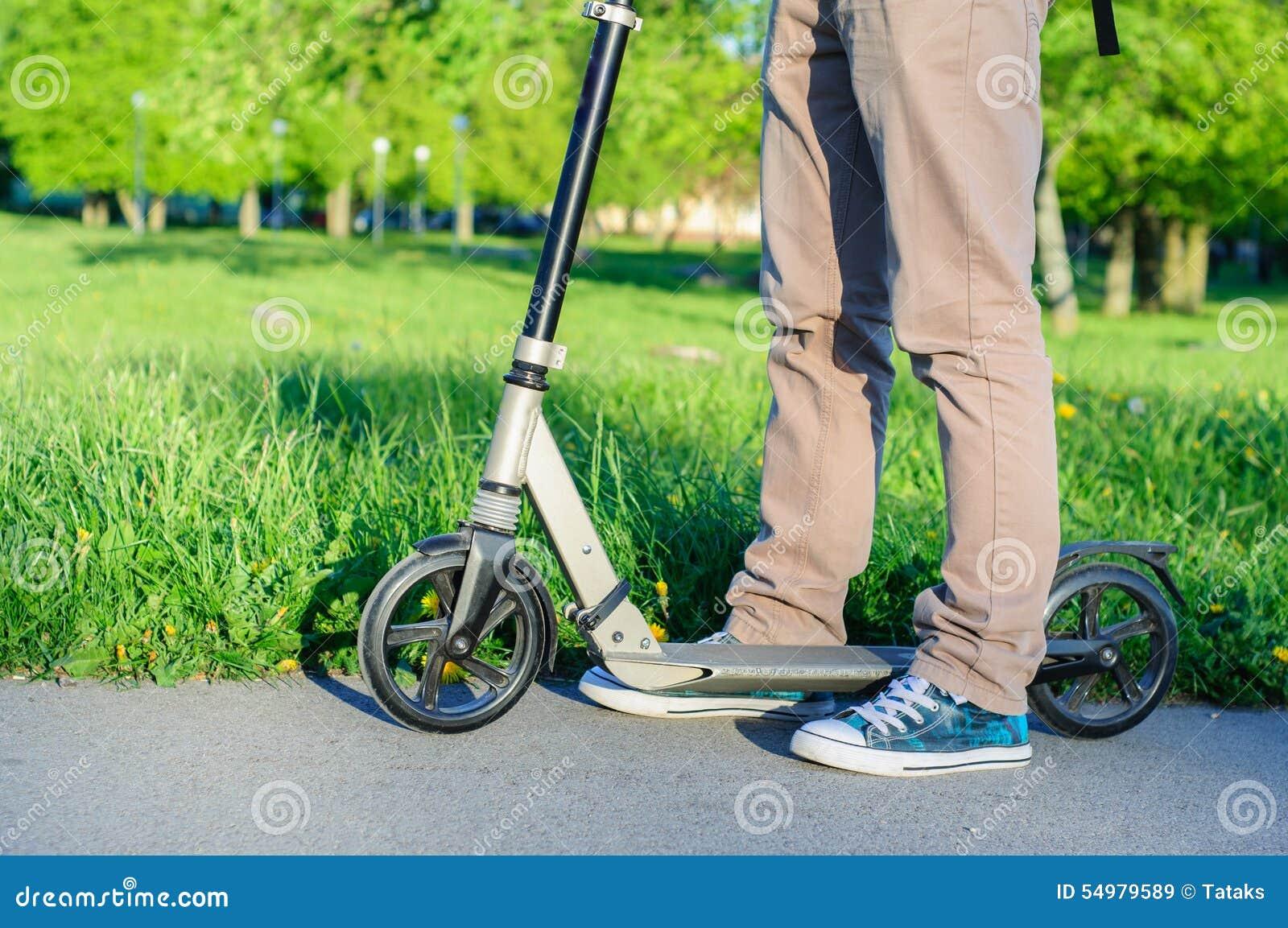 Den unga mannen i tillfälliga kläder på sparksparkcykeln parkerar in