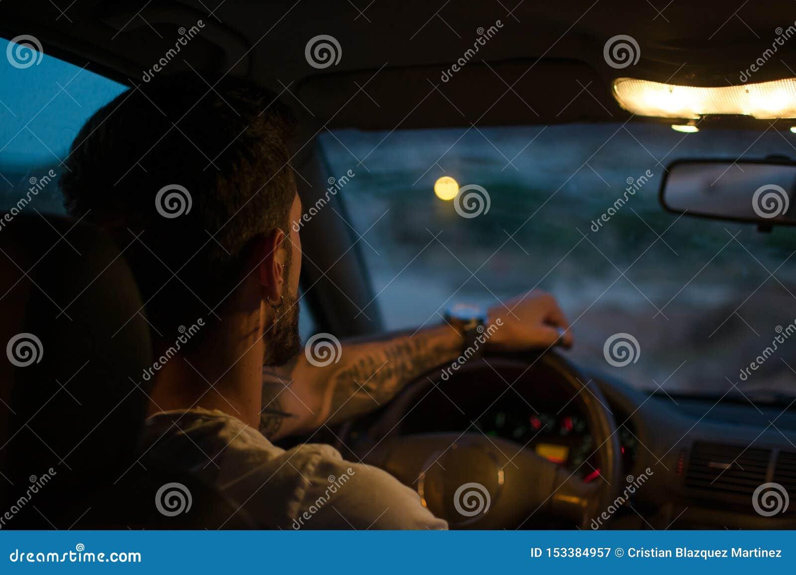 Den unga mannen med örhängen kör en bil på natten