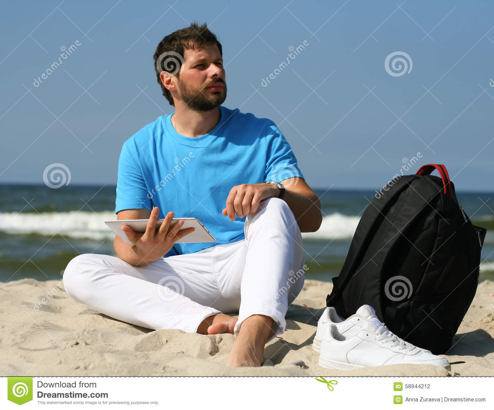 Den unga mannen med bärbara datorn och ryggsäcken under stranden semestrar