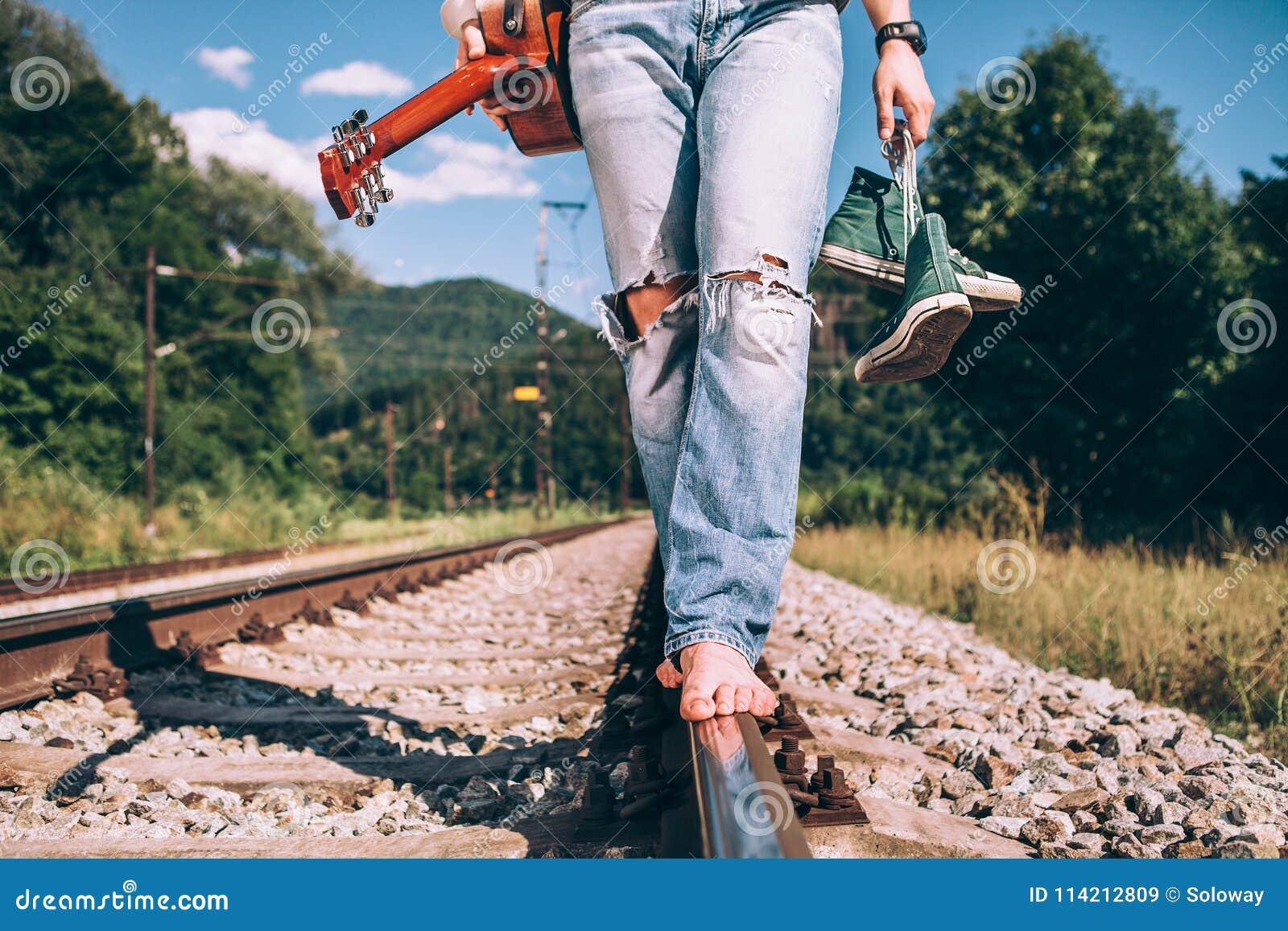Den unga mannen med gitarren går på den järnväg vägen, ben för slut avbildar upp