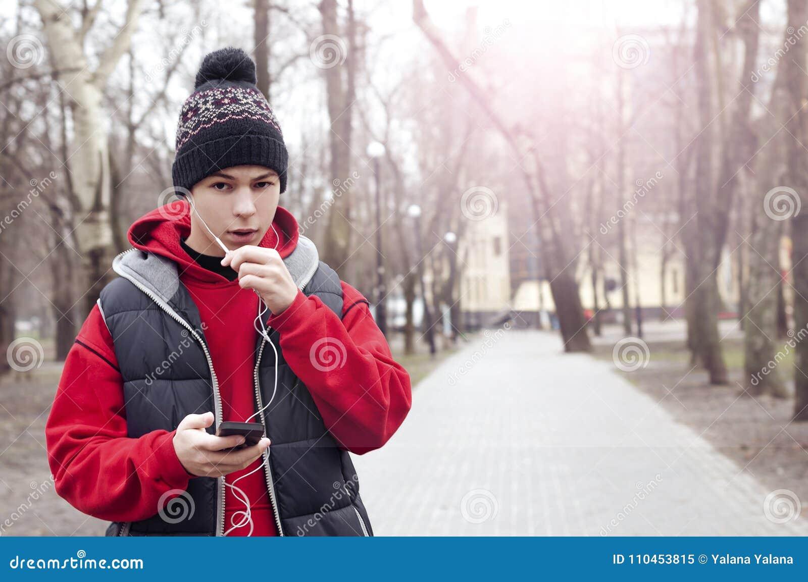 Den unga mannen med mobiltelefonen i stad parkerar