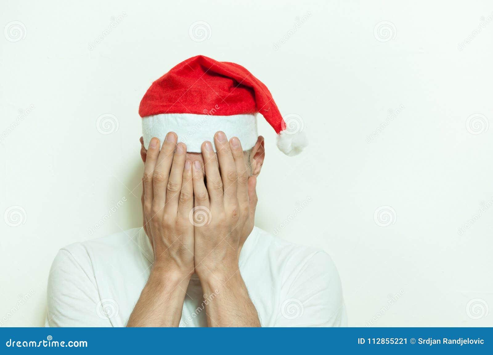 Den unga mannen med den Santa Claus hatträkningen hans framsida med hans händer som känner sig ensamma och ledsna för nytt år och