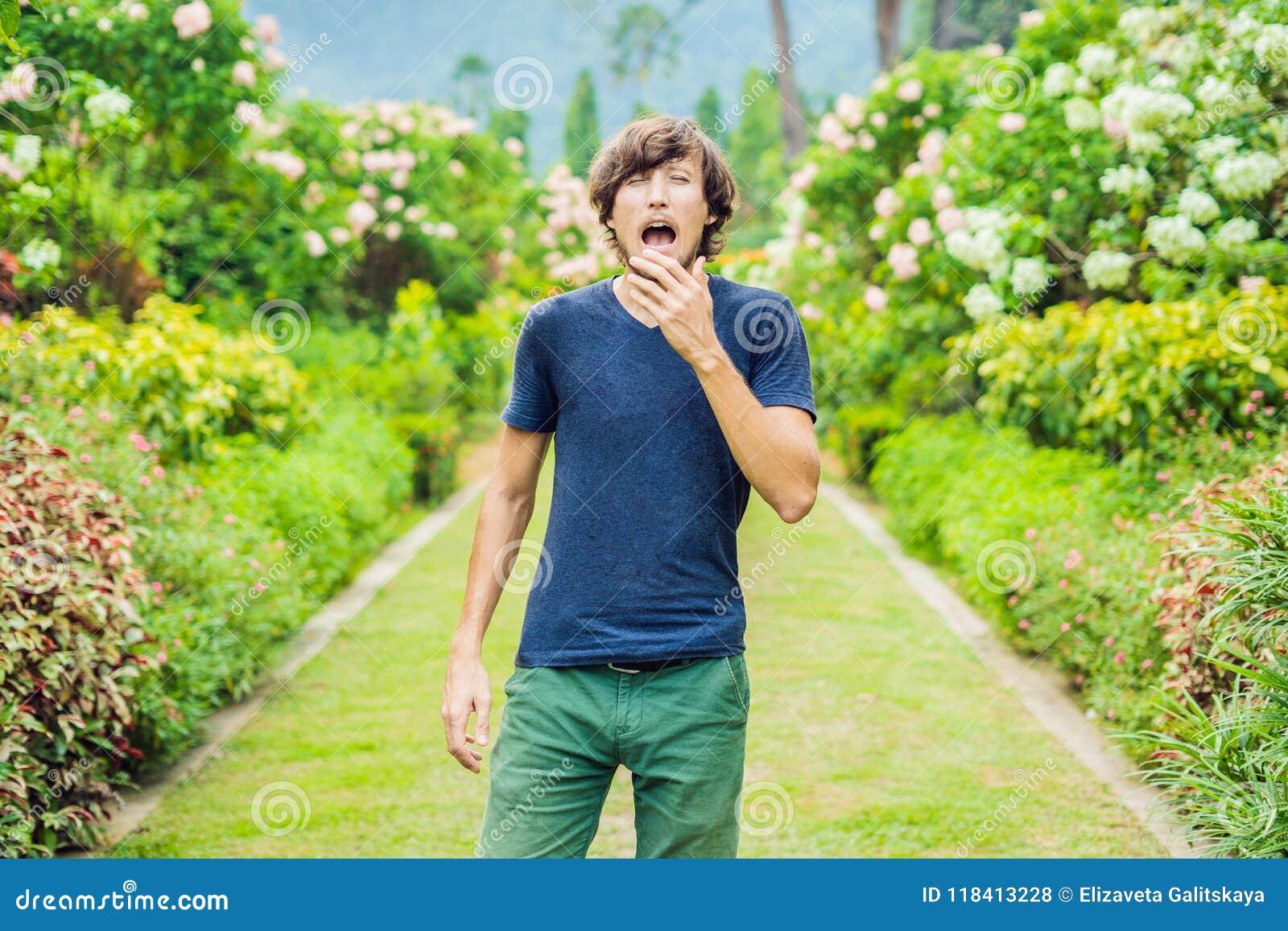 Den unga mannen nyser i parkera mot bakgrunden av en floweri