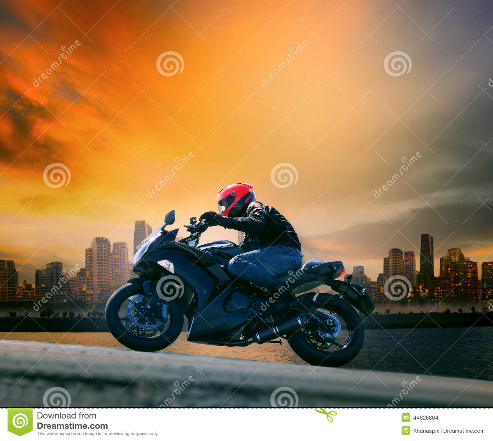 Den unga mannen och säkerhet passar rida den stora motorcykeln mot beautifu