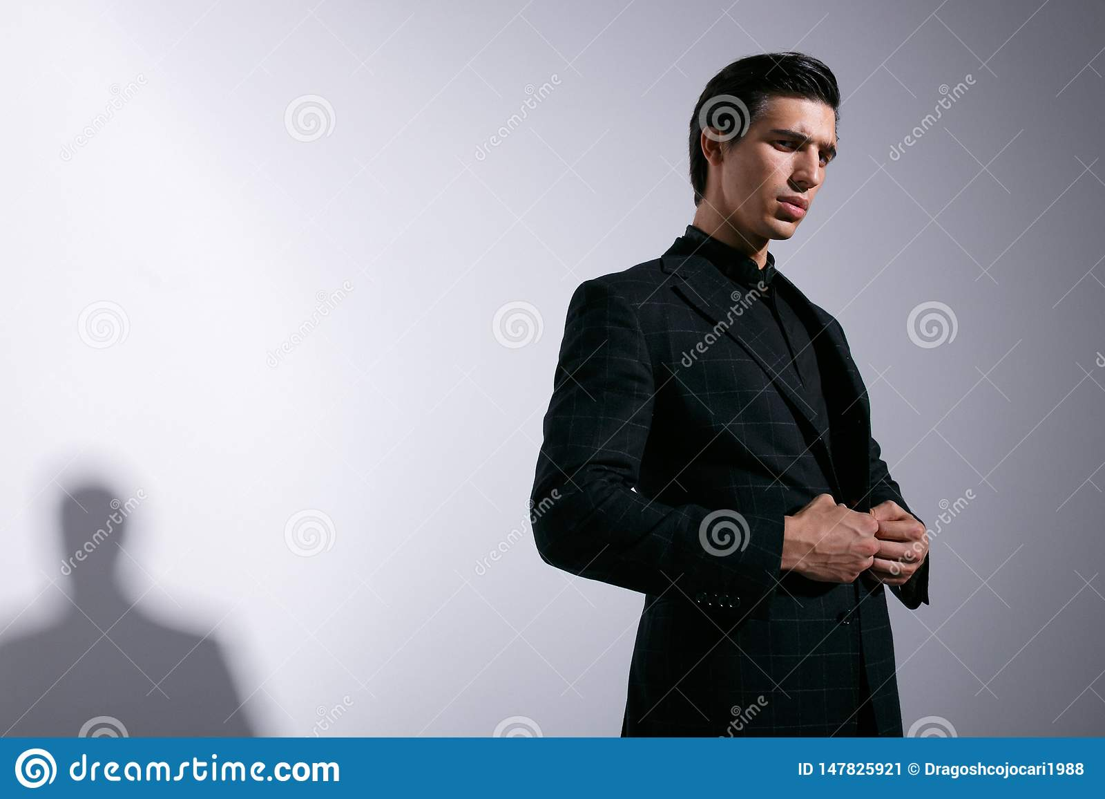 Den unga mannen poserar i studio med attitudine och att se kameran som justerar hans dräkt som isoleras på vit bakgrund