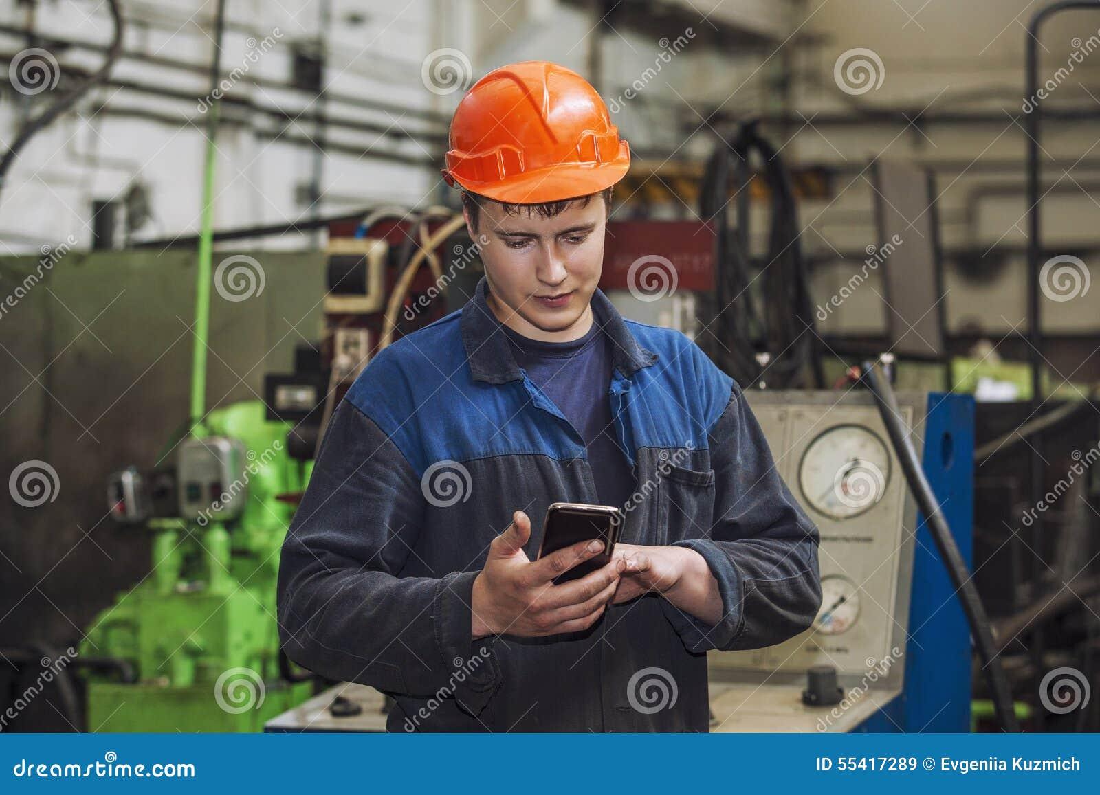 Den unga mannen som arbetar på den gamla fabriken på installation av equien