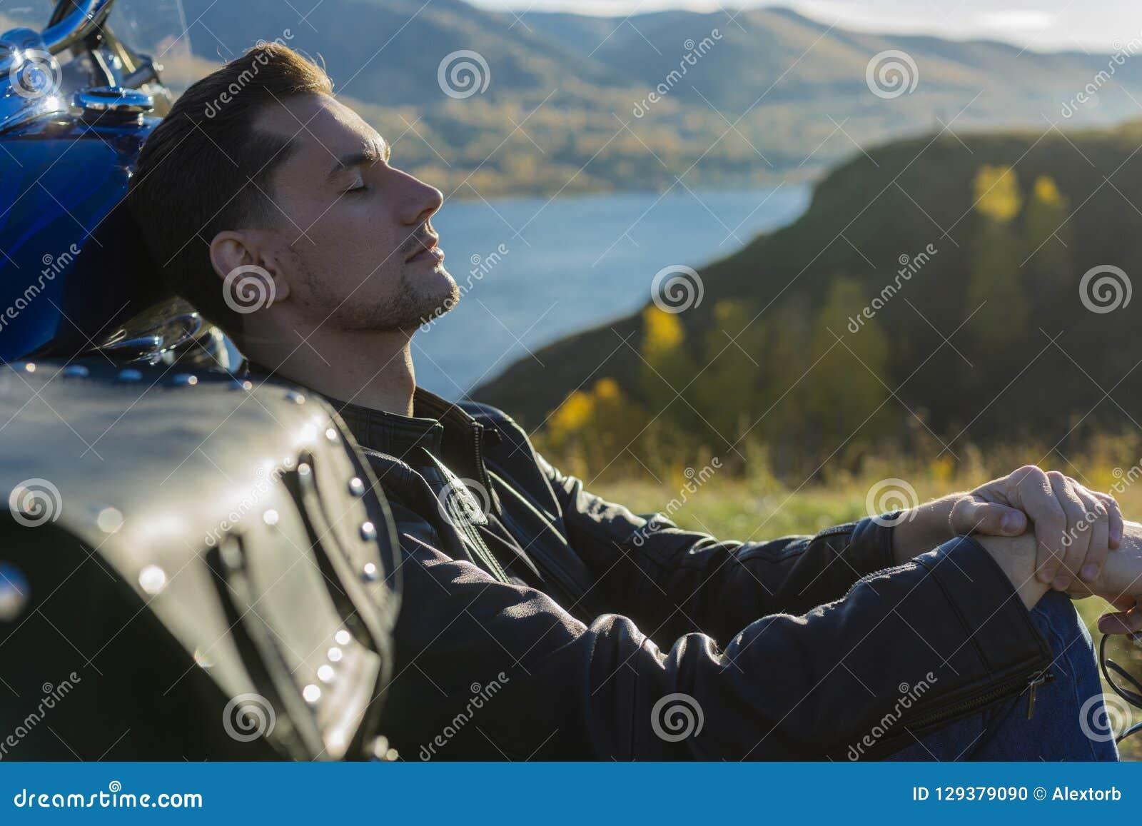Den unga mannen som bär ett svart läderomslag och jeans, sitter utomhus-