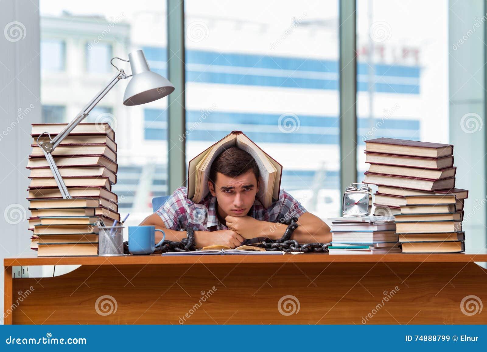 Den unga mannen som förbereder sig för avläggande av examenexamina i högskola