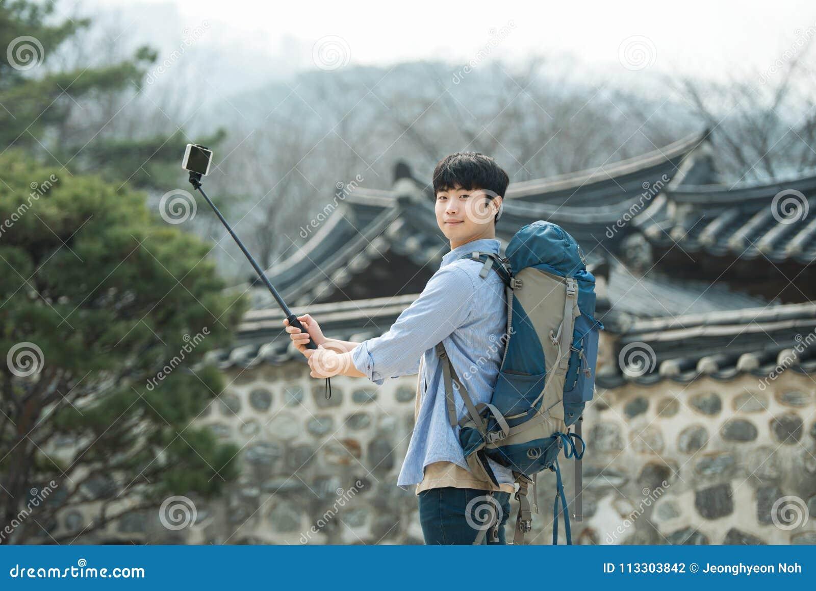 Den unga mannen, som reser till Korea, tar bilder genom att använda hans smartphone