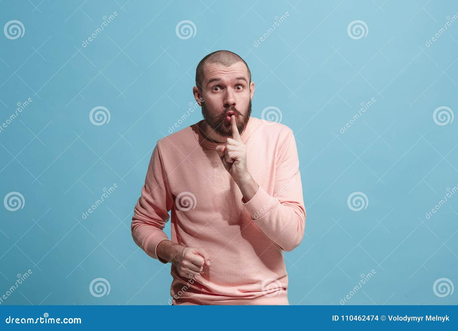 Den unga mannen som viskar en hemlighet bak hennes hand över blå bakgrund