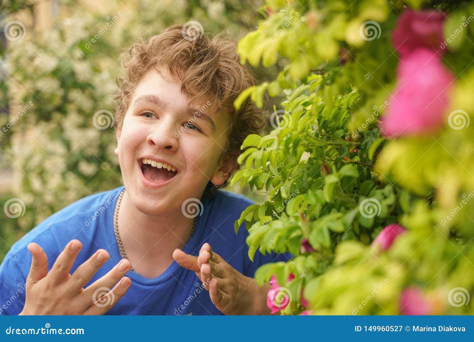Den unga mannen står bland blommorna och tycker om sommar och att blomma