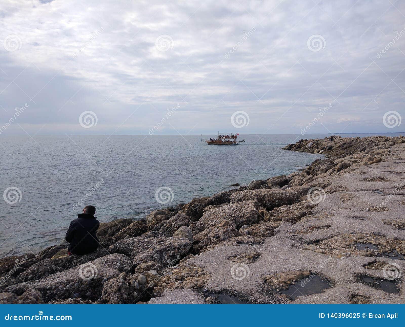 Den unga mannen tänker i en sjö