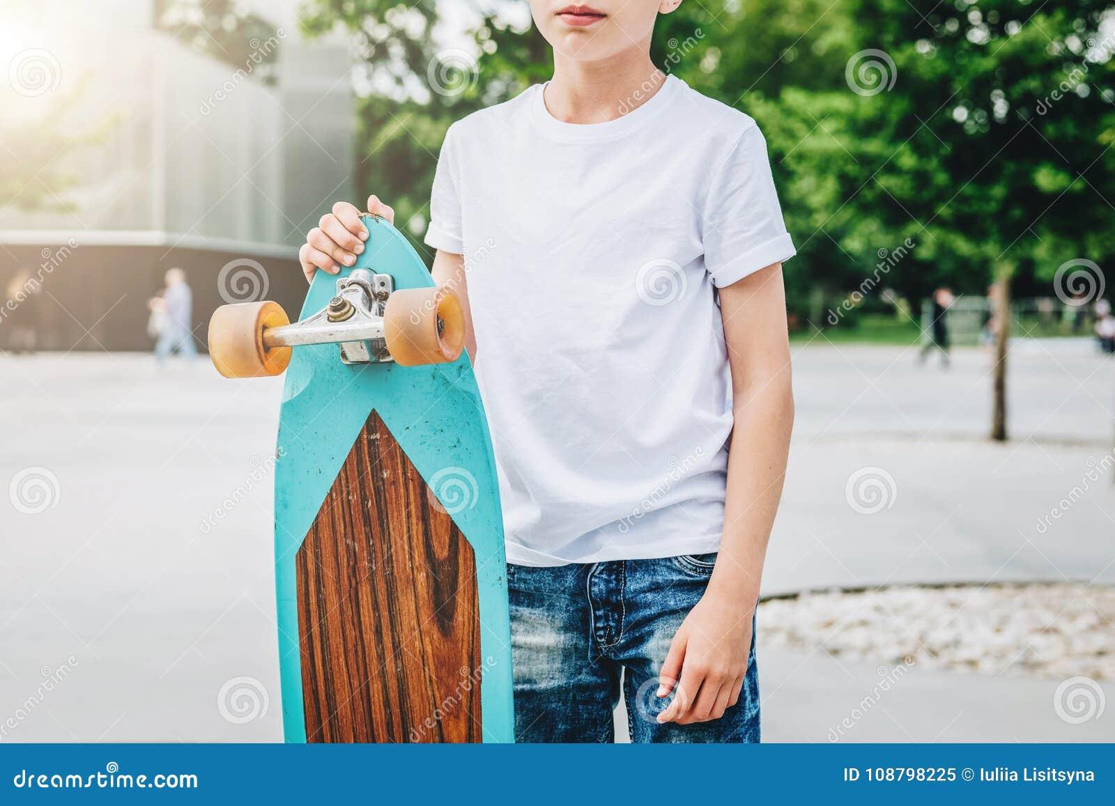 Den unga millennial t-skjortan för iklädd vit för pojken är utomhus- ställningar Åtlöje upp Utrymme för logoen, text, bild
